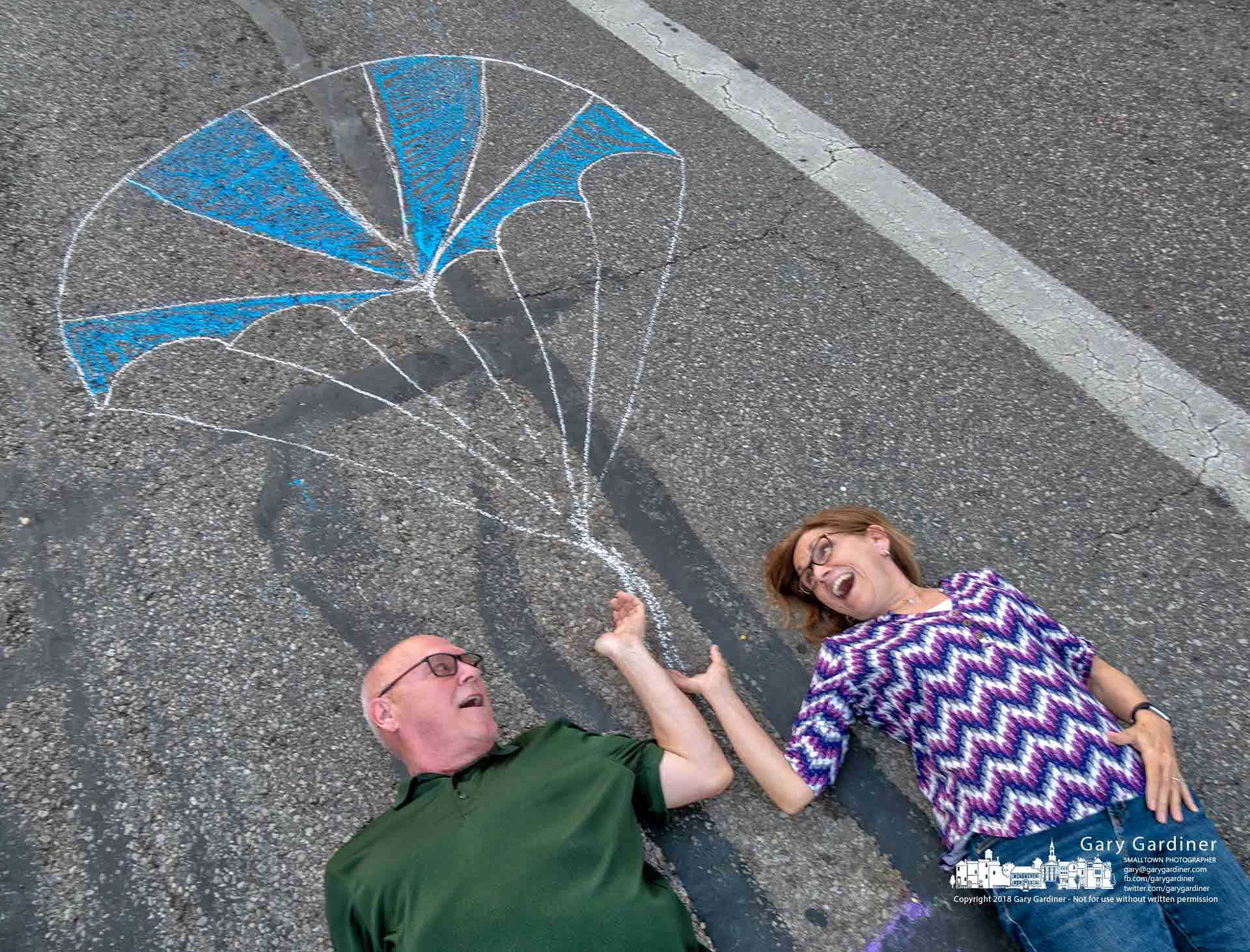 A pair of older kids lies in the middle Statete Street pretending to be suspended in midair by a make-believe parachute sketched in chalk during Fourth Friday in Uptown Westerville. My Final Photo for May 25, 2018.