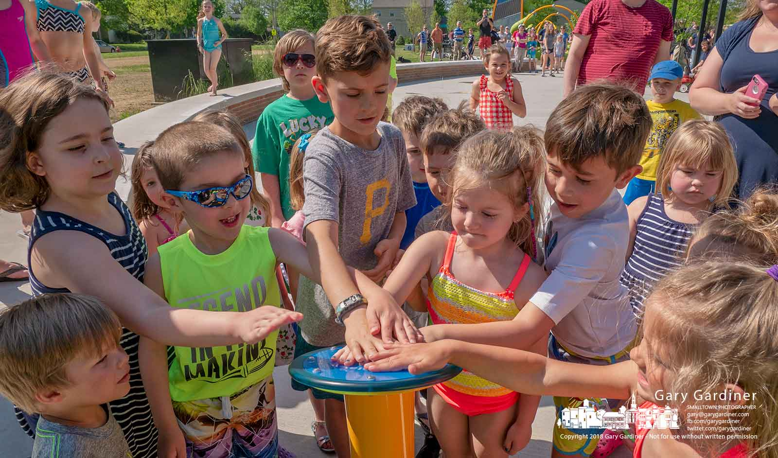 Kids crowd the waterproof button preparing to start the new splash pad water fountain at the grand opening of the new Hanby Park behind the library. My final Photo for May 12, 2018.
