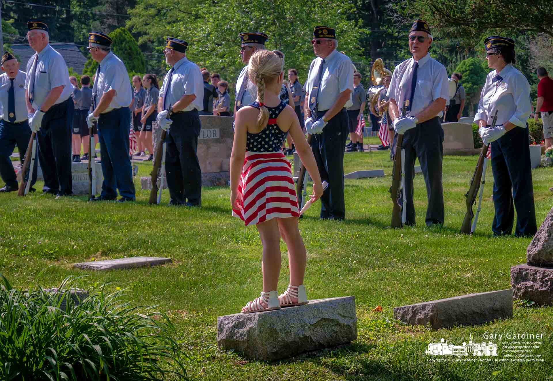 A young girl settles onto the perch she thinks is best to retrieve spent brass from the American Legion Honor Guard FiringSquad during Memorial Day ceremonies at Otterbein Cemetery in Westerville. My Final Photo for May 28, 2018.