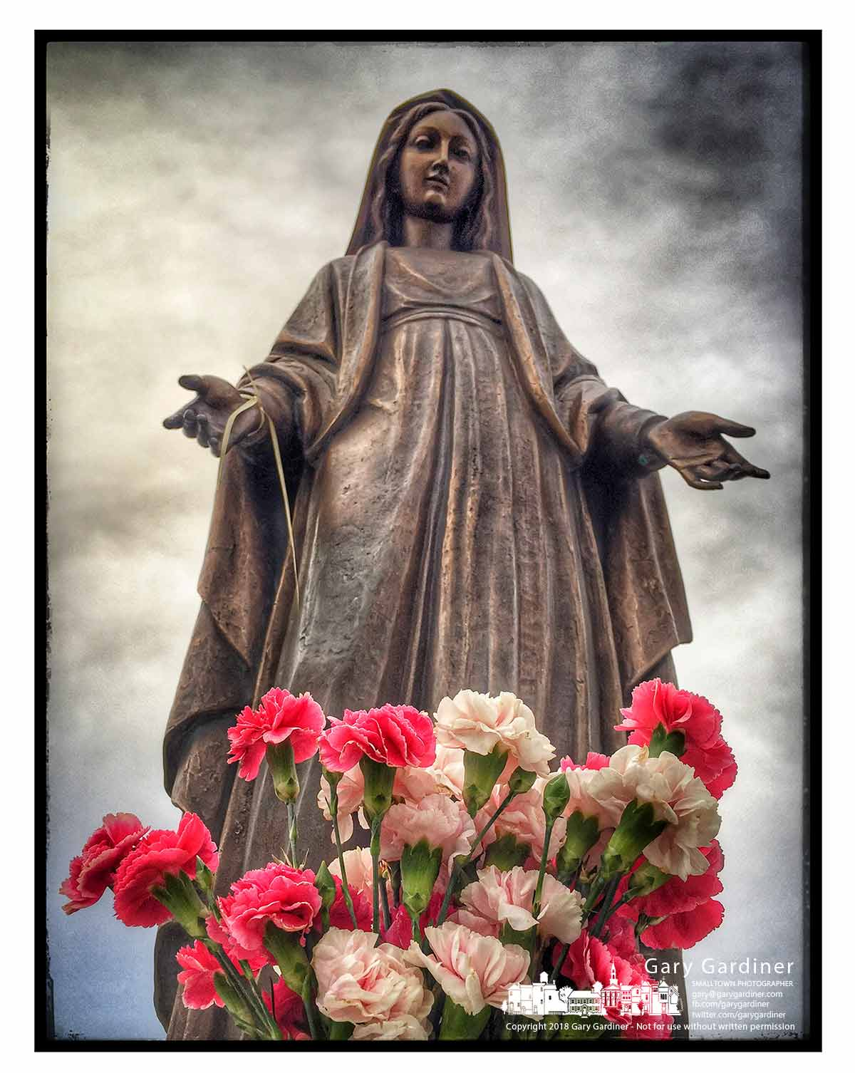 Flowers left by a parishioner sit at the feet of the statue of Mary at the shrine near the entrance to St. Paul the Apostle Catholic Church in Westerville, Ohio. My Final Photo for May 6, 2018.