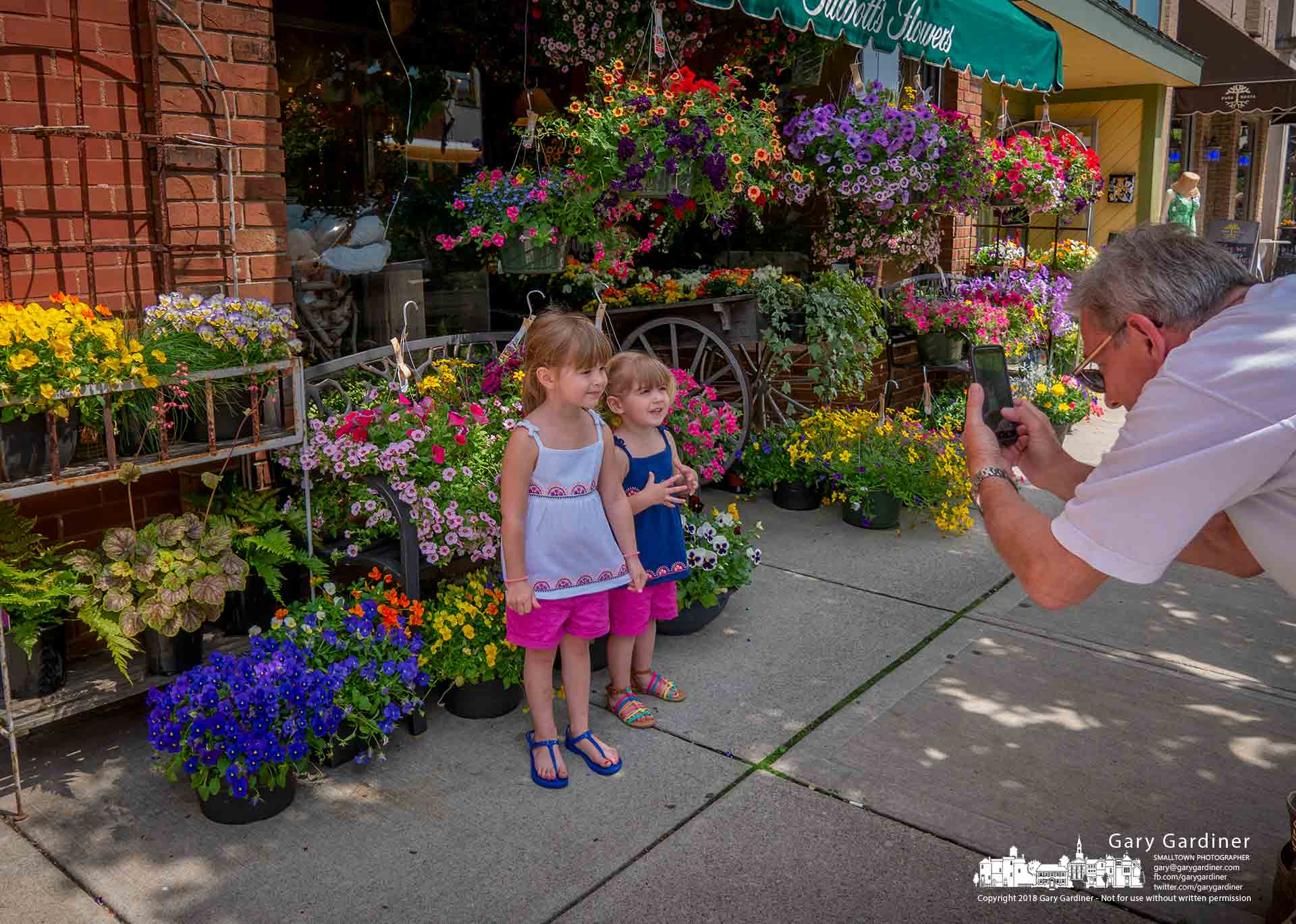 Grandfather uses his smartphone to record a Mother's Day greeting for the mother of two of his granddaughters using the flowers in front of Talbott's Flowers as the background. My Final Photo for May 11, 2018.