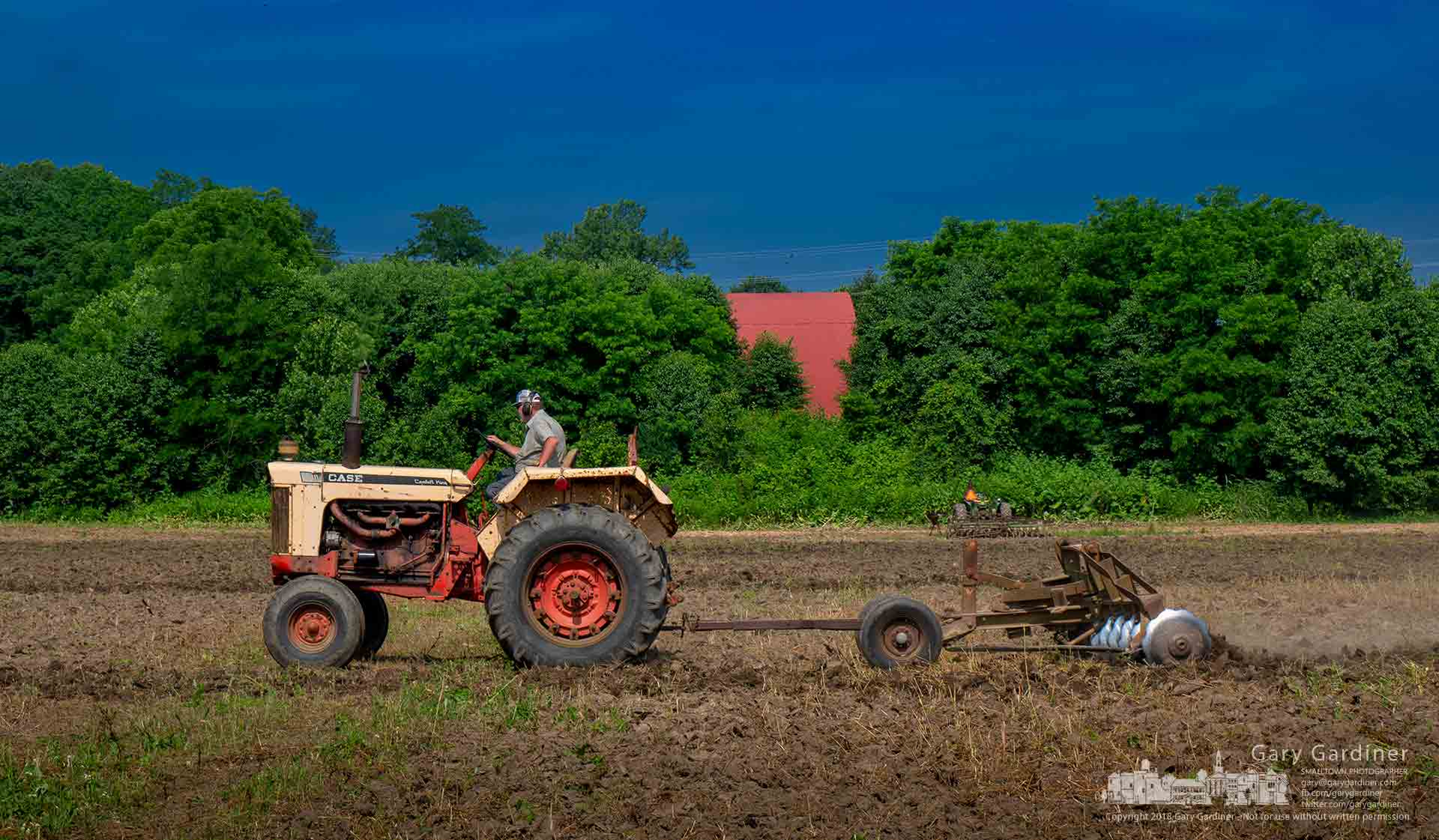 Farmer Tom runs a 12-bladed disc through the main field at the Braun Farm in preparation for planting soybeans a little later than normal. My Final Photo for June 18, 2018.