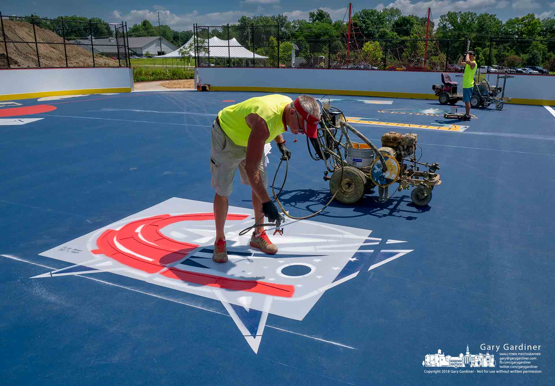 Workers paint logos on the surface of the Thomas Knox hockey rink getting it ready for the dedication Saturday morning. My final Photo for June 29, 2018.