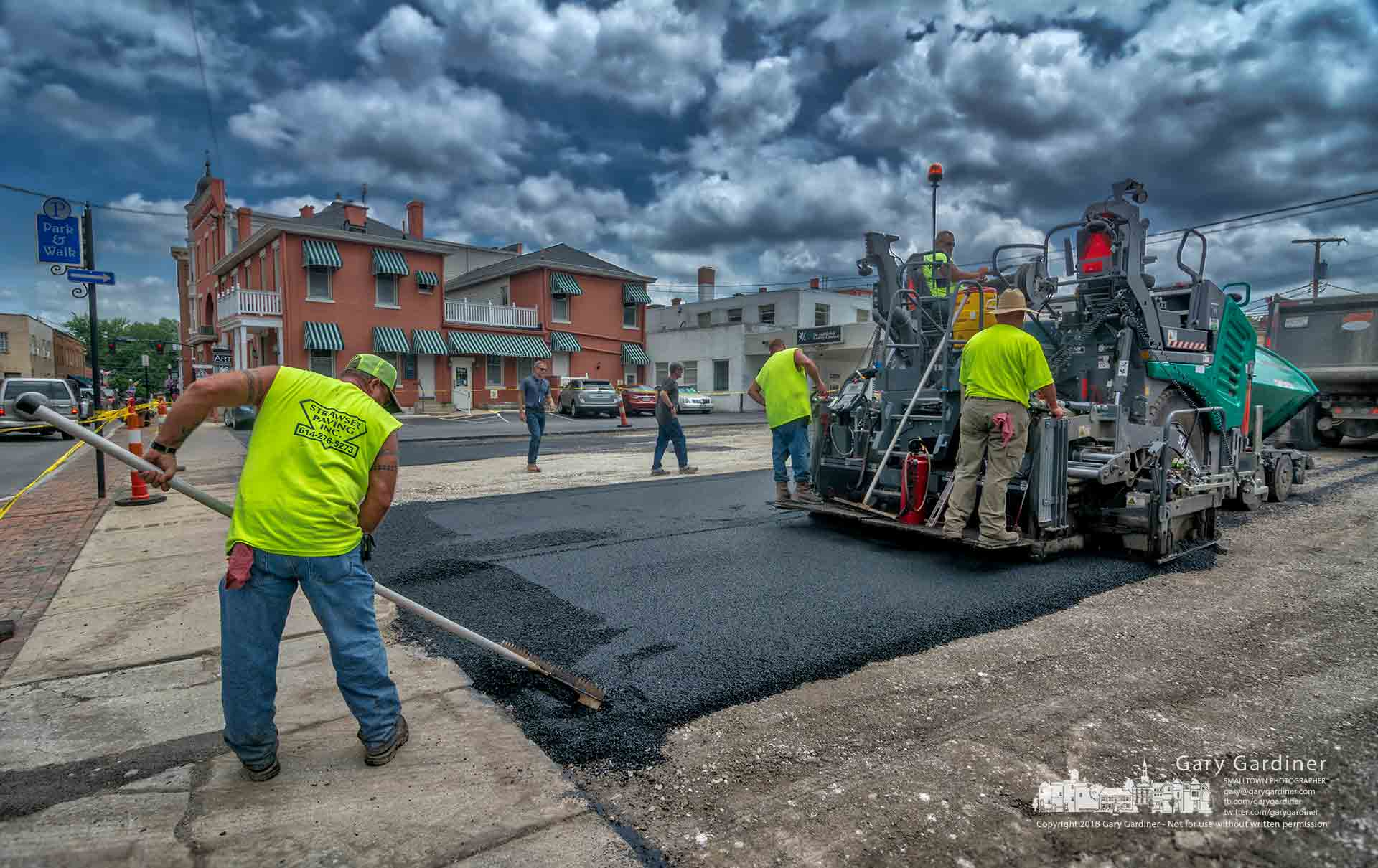 A paving crew begins laying the first layer of asphalt on the parking lot that spans from West College to West Main behind the State Street businesses. My Final Photo for June 26, 2018.