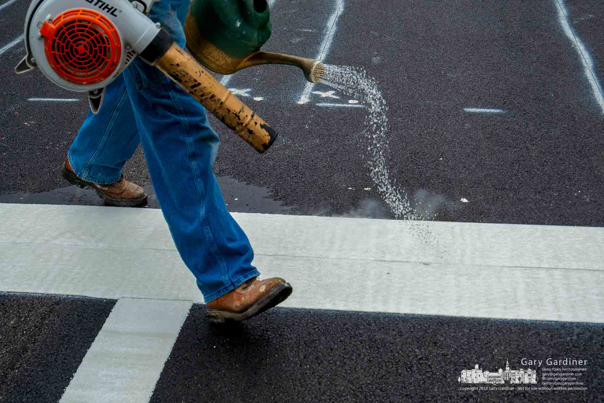 A worker blows away debris and dumps water on fresh striping applied to the new asphalt on Huber Village Blvd. and Allview as resurfacing and curb repairs nears completion. My Final Photo for June 21, 2018.