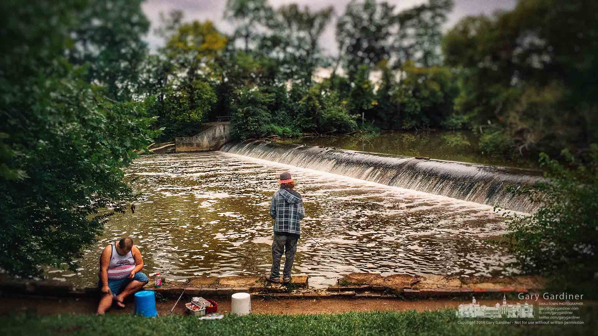 One angler checks his smartphone with his rod settled on the creekbed wall as the other reels his lineacrossthe rapid waters below the Aum Creek spillway in Westerville. My Final Photofor July 31, 2018.