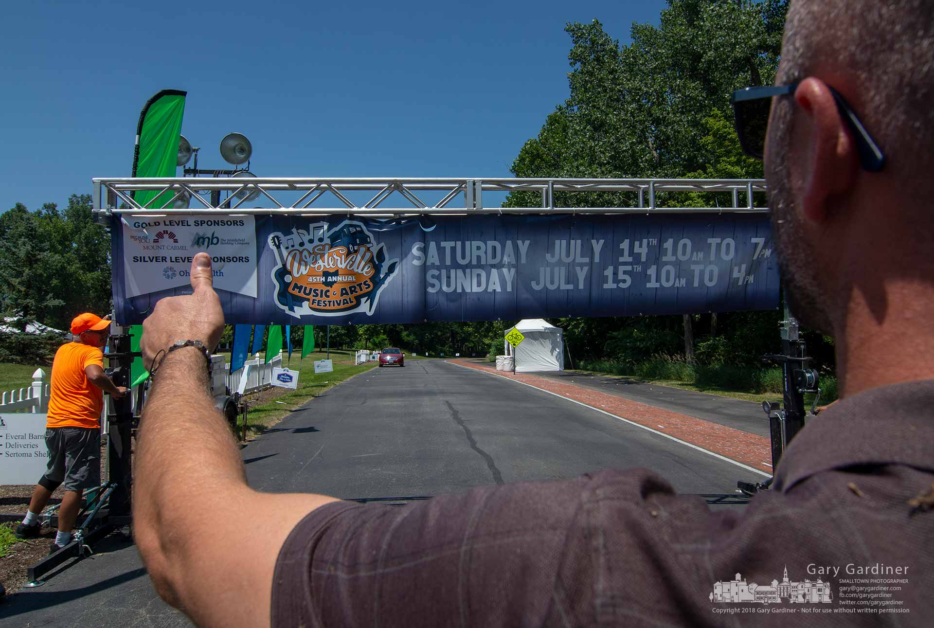 Matt Ulry signals thumbs-up as helpers level support girders before raising the Westerville Music And Arts Festival banner over Lindimore Way, the roadway that runs through the park where the festival opens Saturday. My Final Photo for July 13, 2018.
