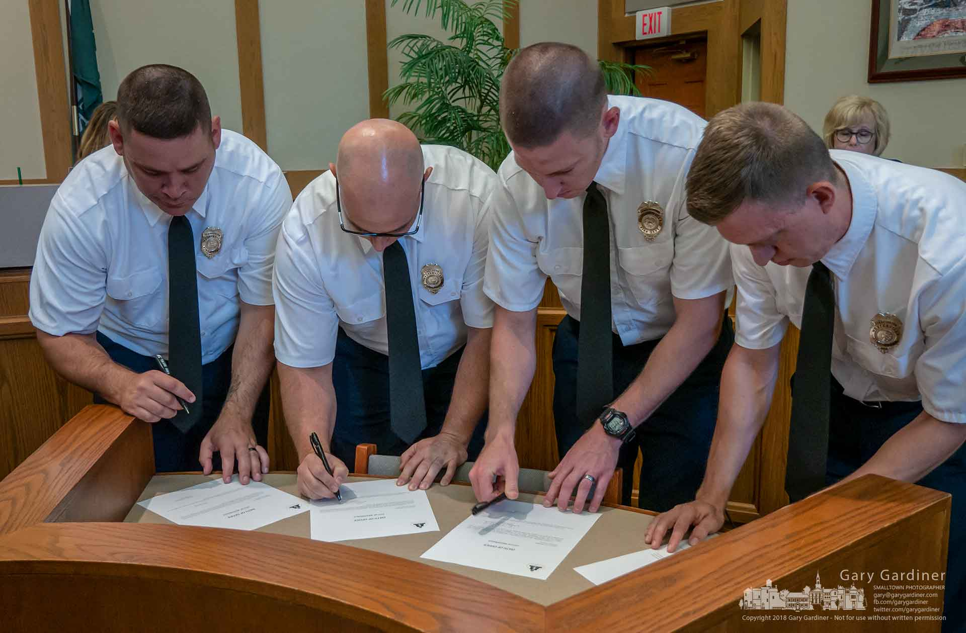 Westerville's newest firefighters, from left, Ryan Wamsley, Andrew Taylor, Andrew Saunders, and Stephen Burger, sign paperwork making their assignments as Westerville firefighters official after being sworn in at City Council. My Final Photo for July 2, 2018.