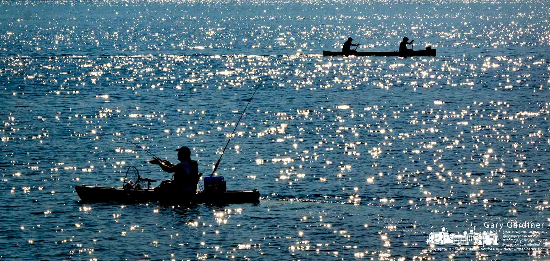 A fishing kayakerand a pair of canoeing anglers navigateopposite directions on the early morningsparkling watersof Hoover Reservoir. My Final Photo for July 28, 2018.