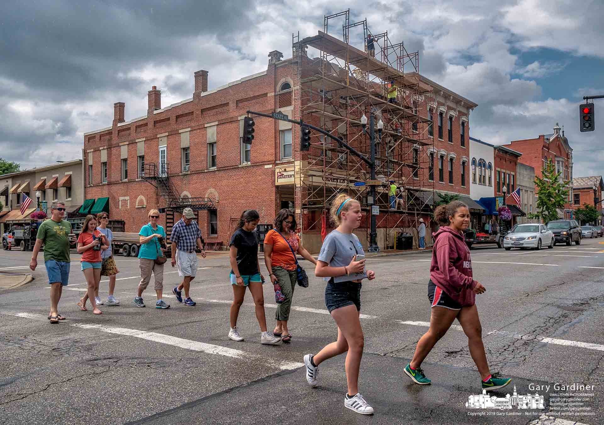 Monday shoppers cross State Street across the intersection from Graeter's where workers are installing scaffolding as the first step in restoring the original parapets that once topped the front of the building. My Final Photo for July 23, 2018.