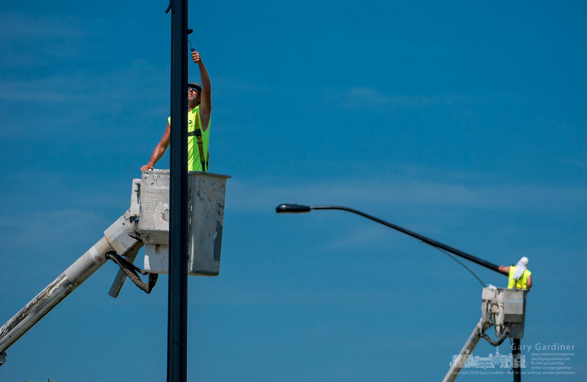 Workers paint the light poles black on County Line Road near Cleveland Ave. as part of a contract to refurbish that section of the roadway. My Final Photo for July 3, 2018.