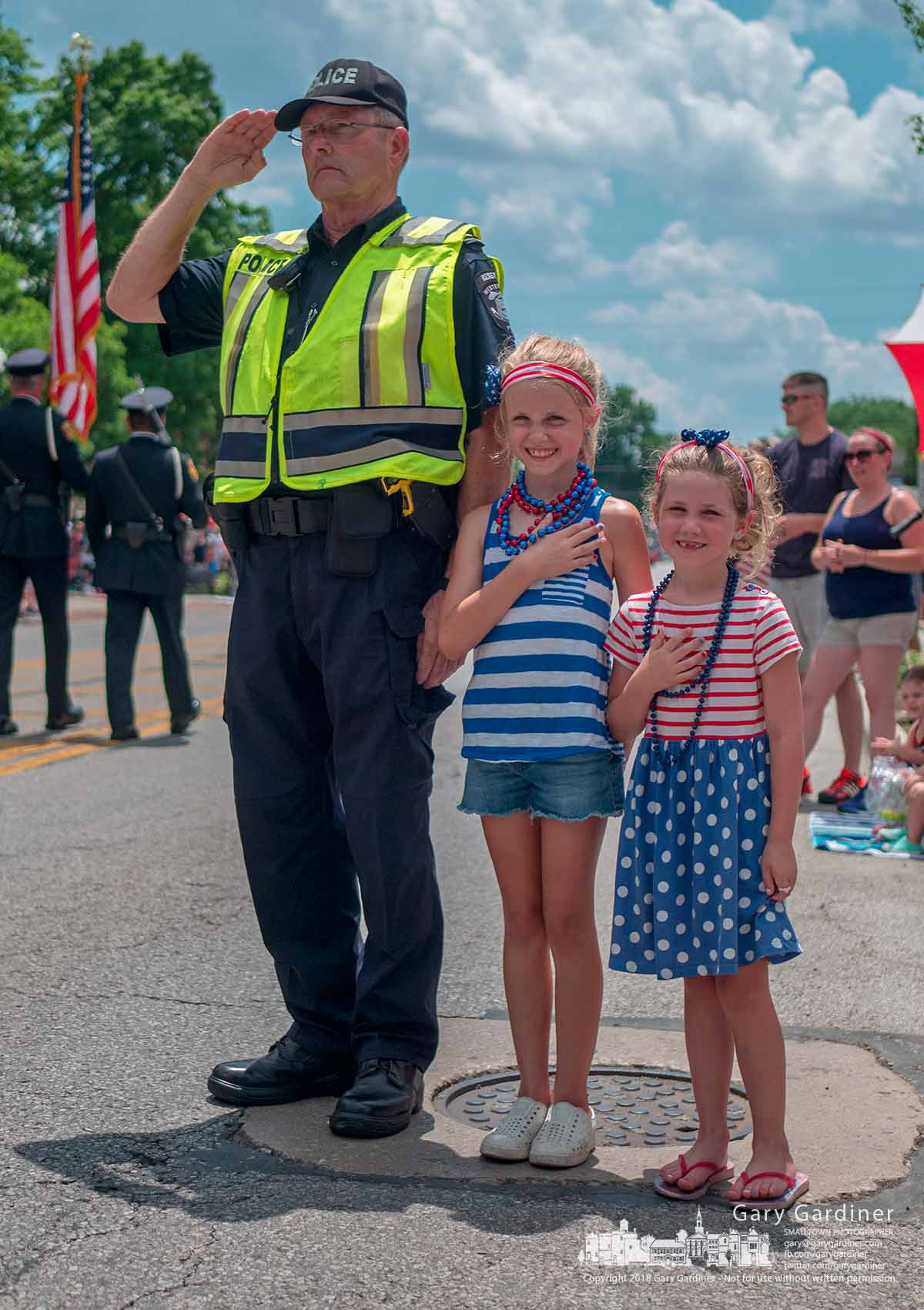 Westerville Reserve Police Officer Ted Bretthauer with two young girls by his side salutes the Honor Guard leading the Westerville July 4th parade. My Final Photo for July 4, 2018.