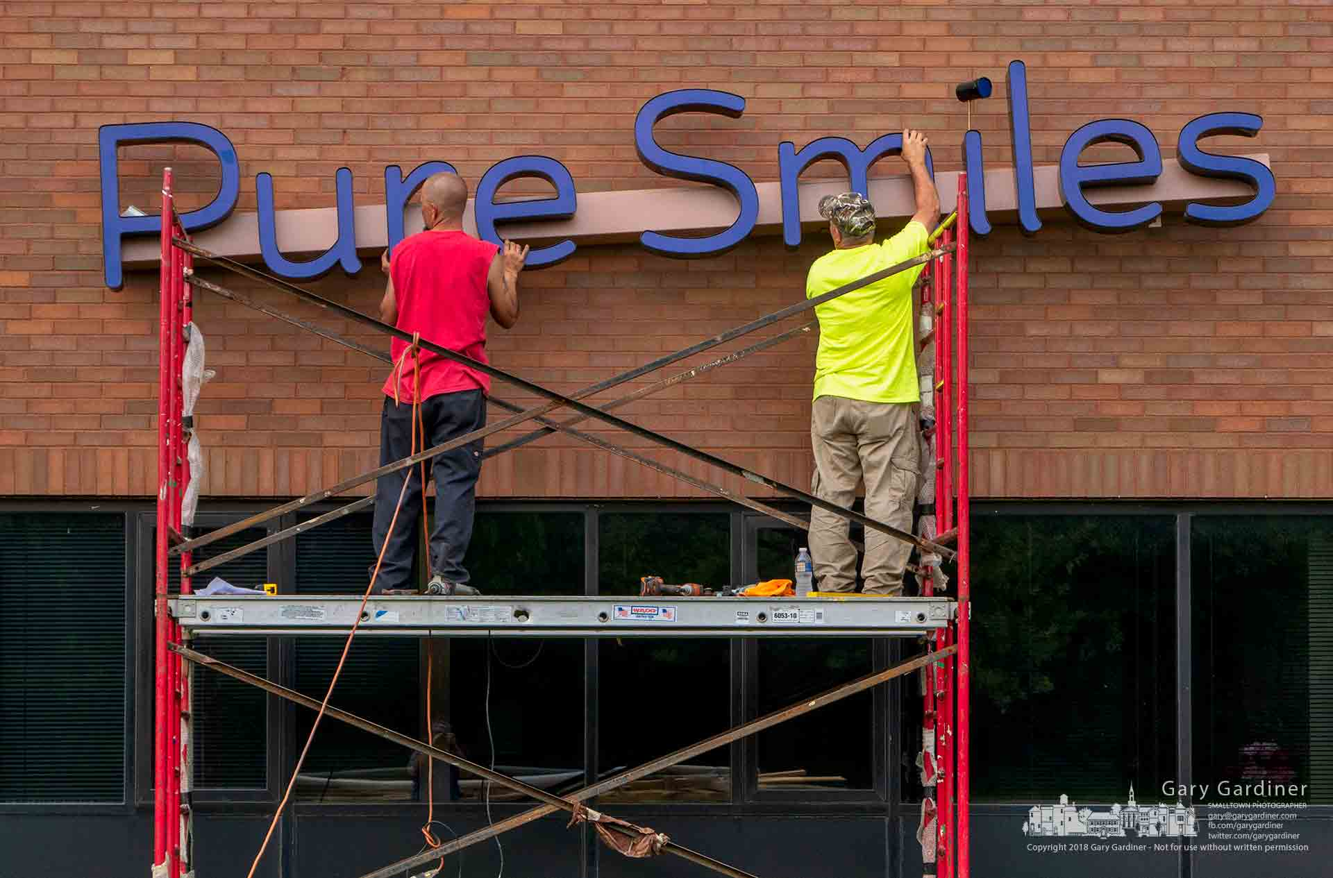 Sign workers adjust the position of the sign for a dental office being attached to the side of the building at Dempsey and Sunbury Roads. My Final Photo for July 30, 2018.