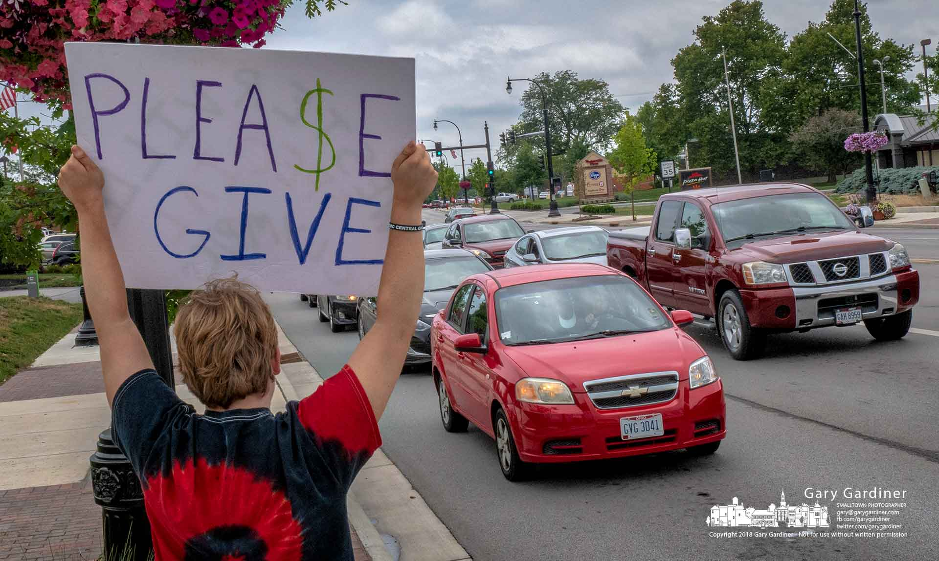 A Special Olympian stands with his sign beside traffic on State Street at Schrock Road where volunteers gathered donations to help fund Westerville Special Olympics. My Final Photo for July 21, 2018.