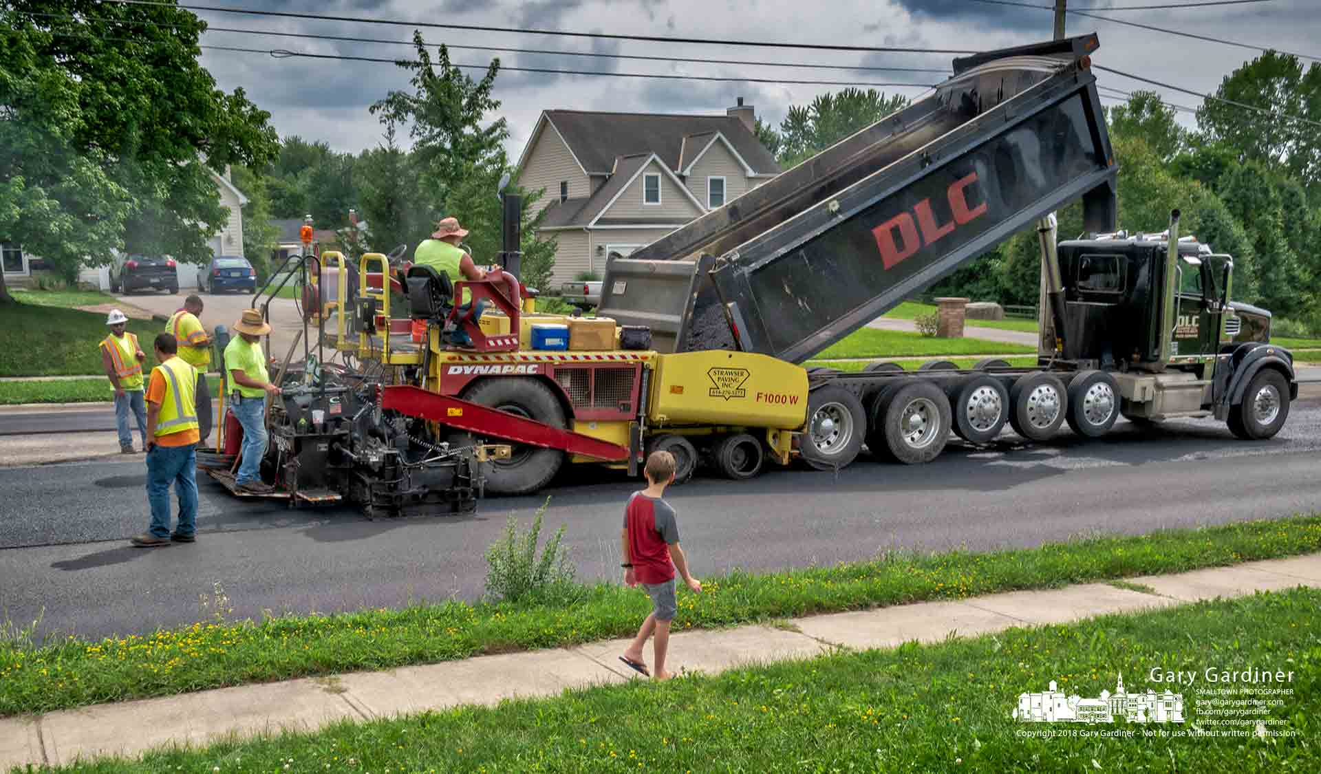 A young boy runs ahead of his family to get a closer look at a paver laying asphalt on County Line Road. My Final Photo for Aug. 2, 2018.