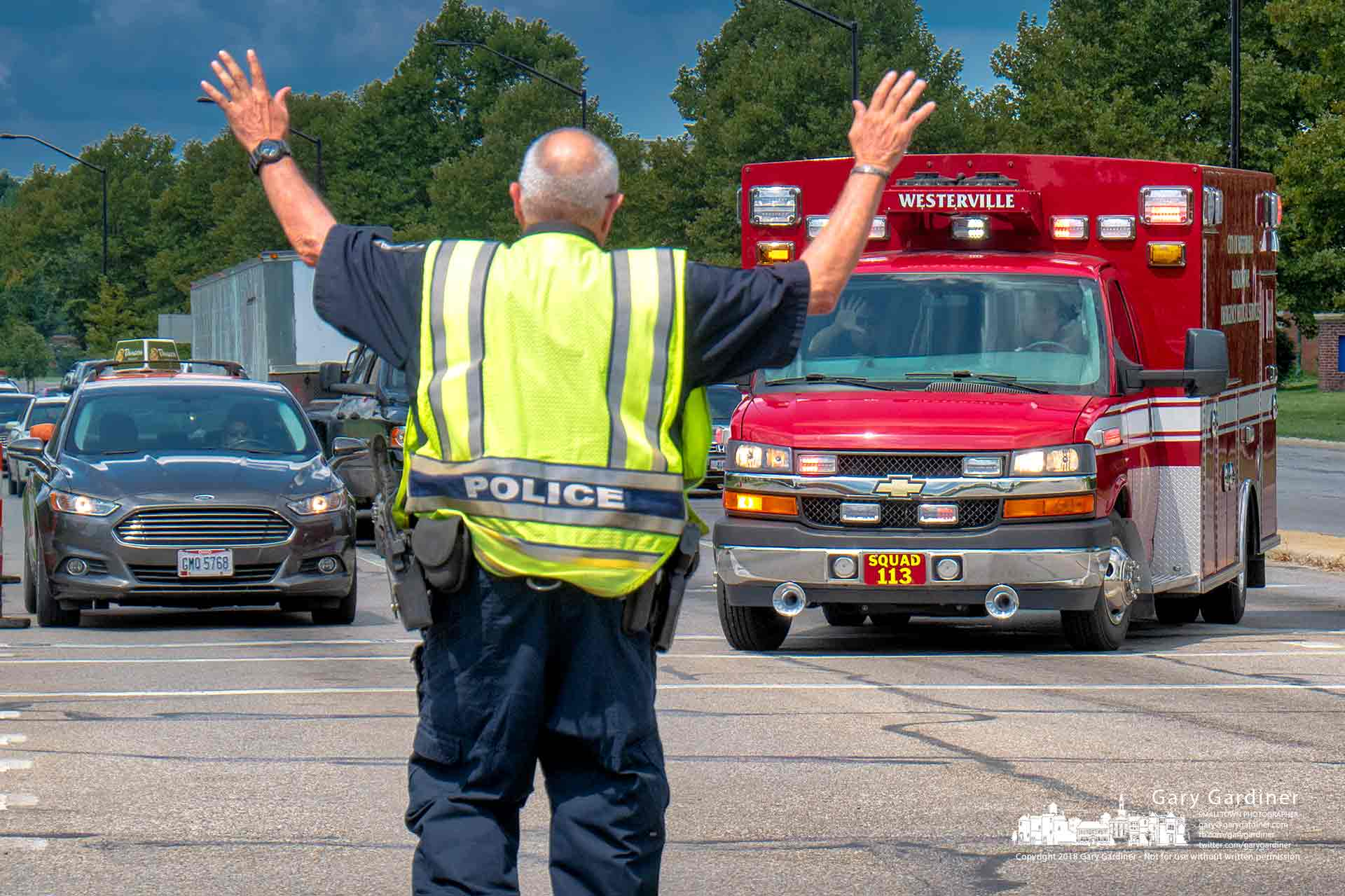 A Westerville Reserve Police Officer stops traffic at Maxtown and State for a fire department emergency squad to navigate around heavy traffic near the road project site. My Final Photo for Aug. 14, 2018.