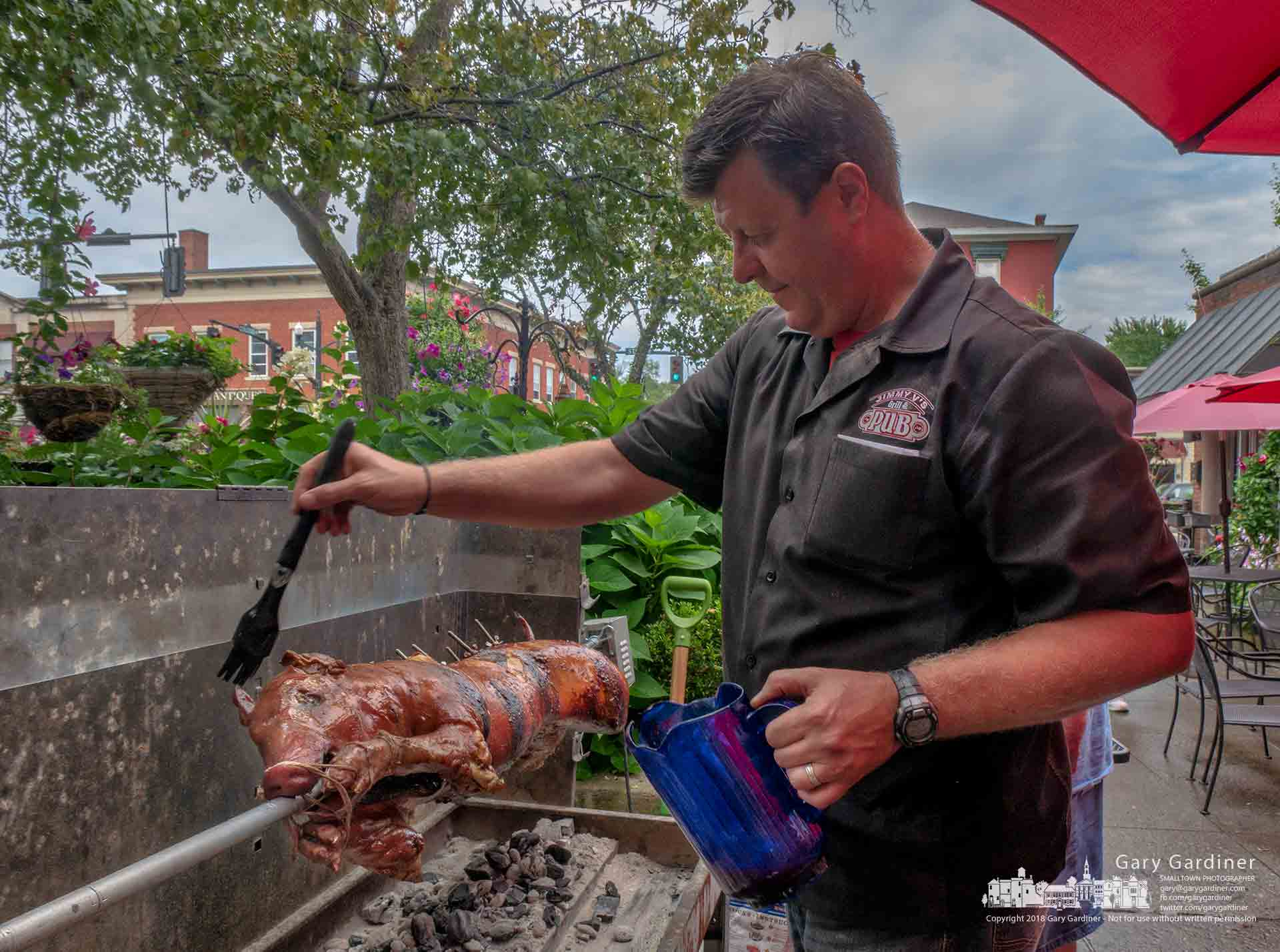Mario Nedelkoski swabs oil on the whole pig he roasted Saturday to celebrate Jimmy V's ninth anniversary in Uptown Westerville. My Final Photo for Aug. 11, 2018.