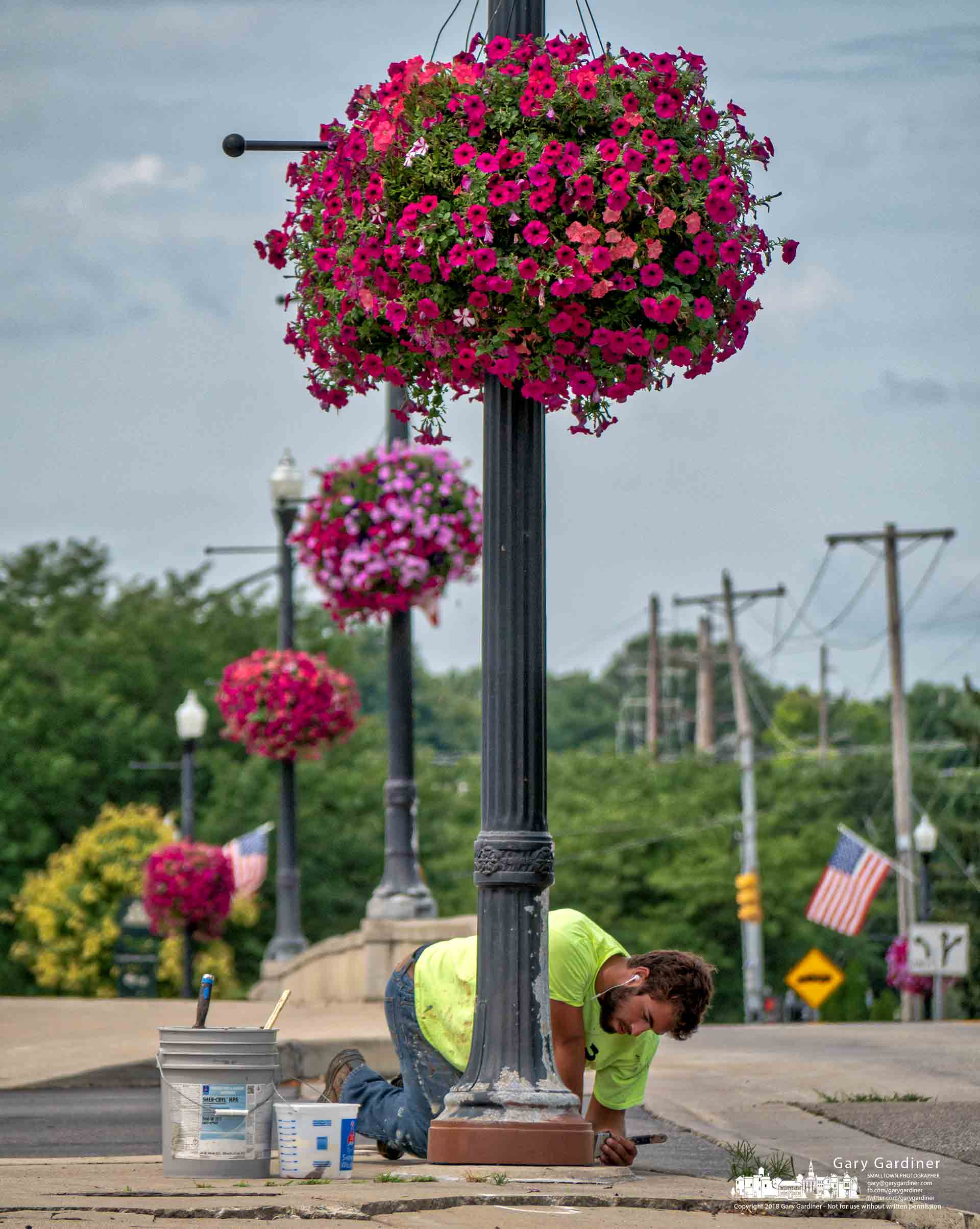 A painting contractor applies brown primer to the green light poles along West Main Street before they are painted black as part of the citymaintenanceprogram. My Final Photo for Aug. 7, 2018.