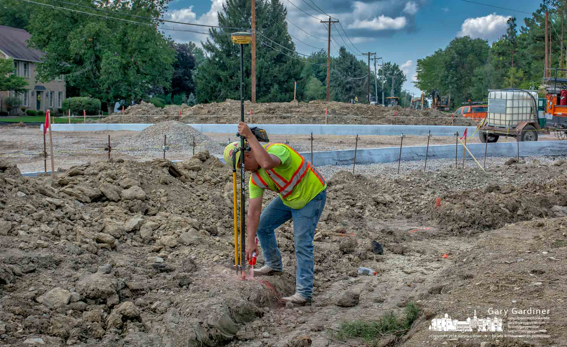 A surveyor marks a spot as he checks elevation and location along the right-of-way for the round-a-bout being built at Smothers and Schott Roads. My Final Photo for Aug. 28, 2018.