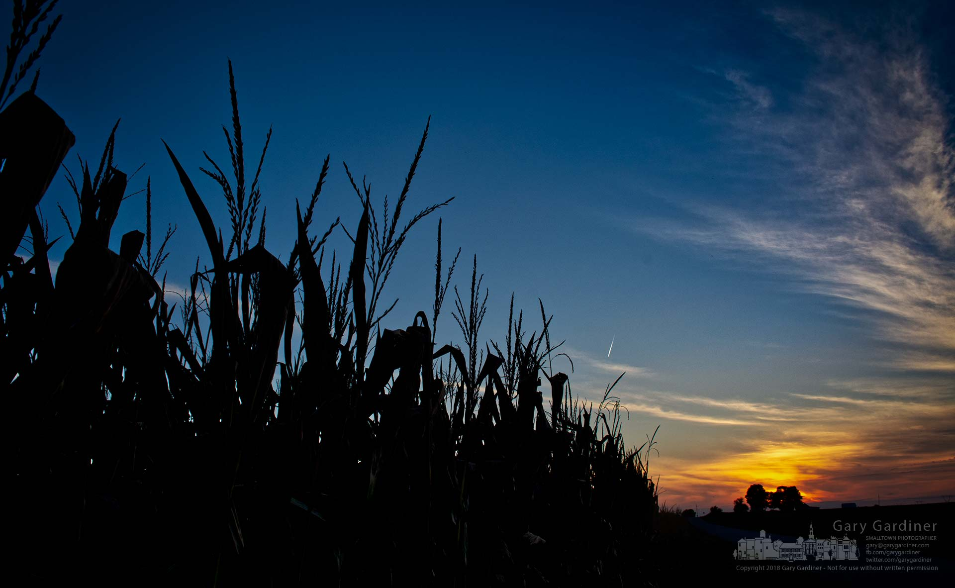 The sun sets behind a farmhouse and field of corn along a country road near Croton, Ohio. My Final Photo for Aug. 30, 2018.