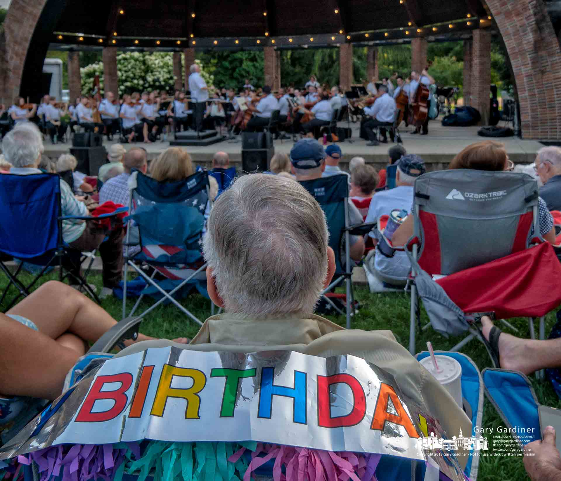 A music lover wearing a banner celebrating his birthday listens as the Westerville Symphony performs a concert honoring the 100th anniversary of the birth of composer Leonard Bernstein at the Alum Creek Amphitheater. My Final Photo for Aug. 19, 2018.