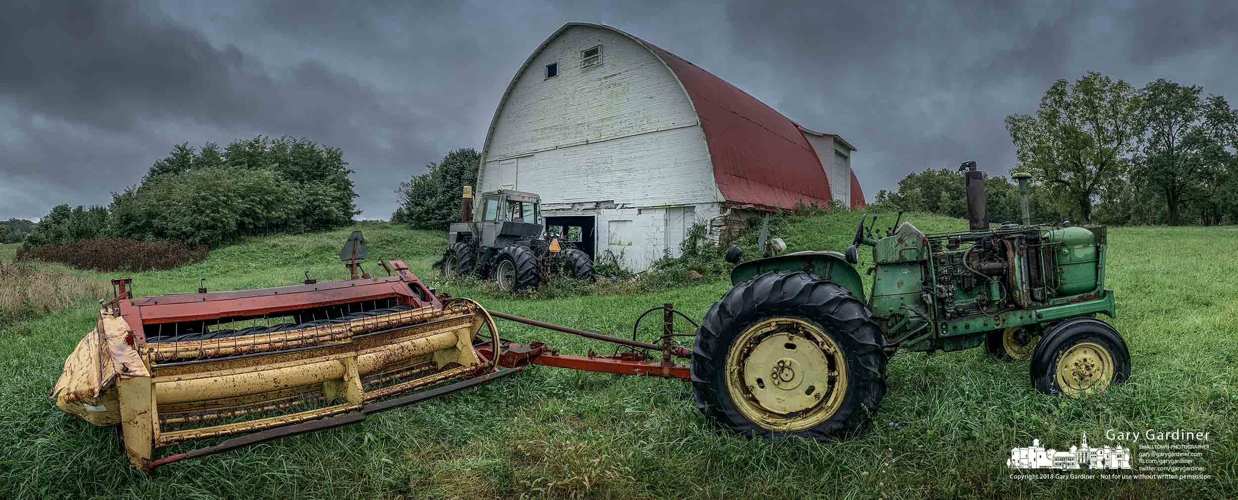 Storm clouds move across the Braun Farm fields where one of the farm's tractors and mower sit idle in the early fall rain. My Final Photo for Sept. 24, 2018.
