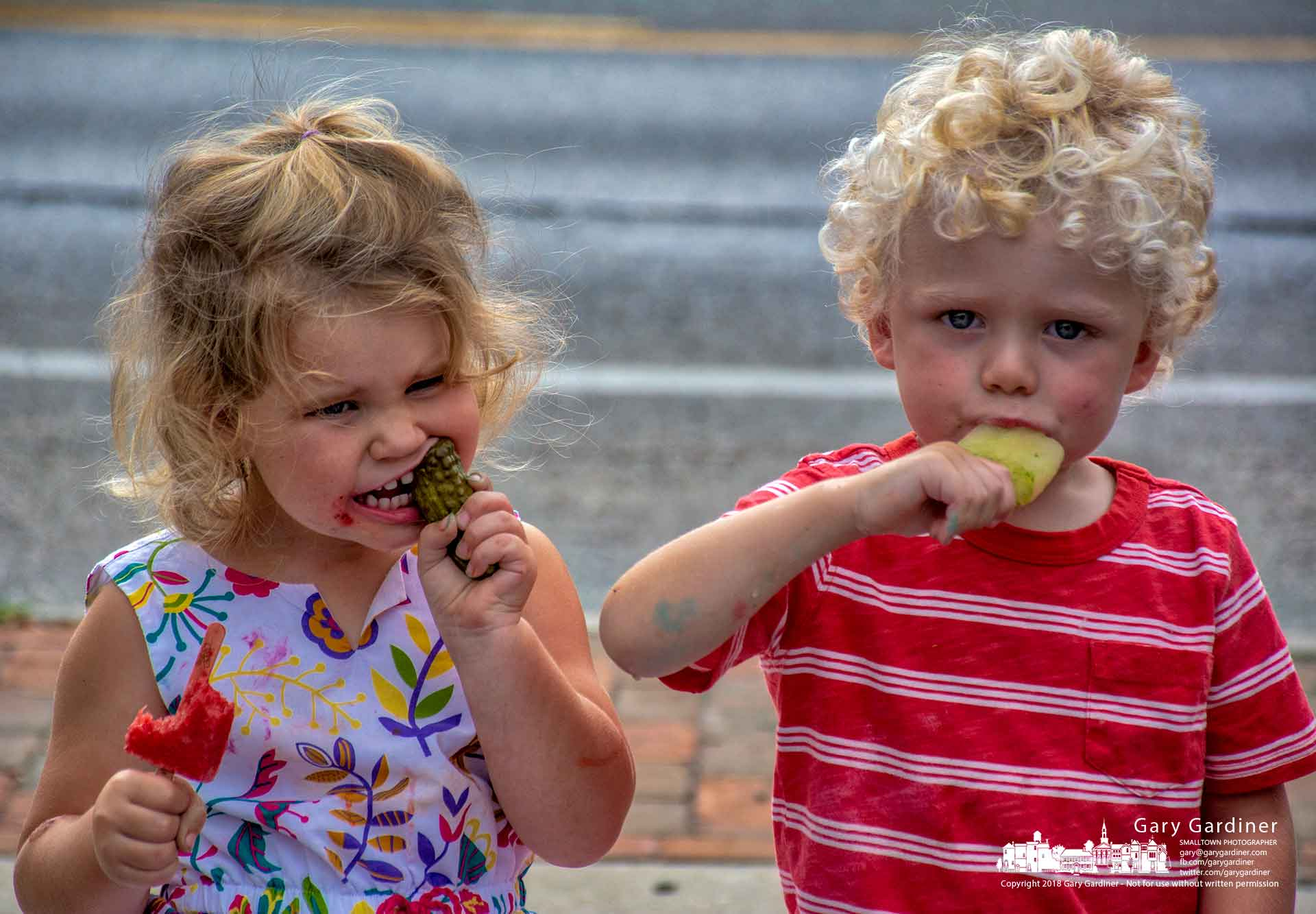 A young couple enjoys J-Pop popsicles as one of them adds the taste of a dill pickle to the flavor mix after their parents shopped at the Upton Westerville Farmers Market Wednesday. My Final Photo for Sept. 5, 2018.