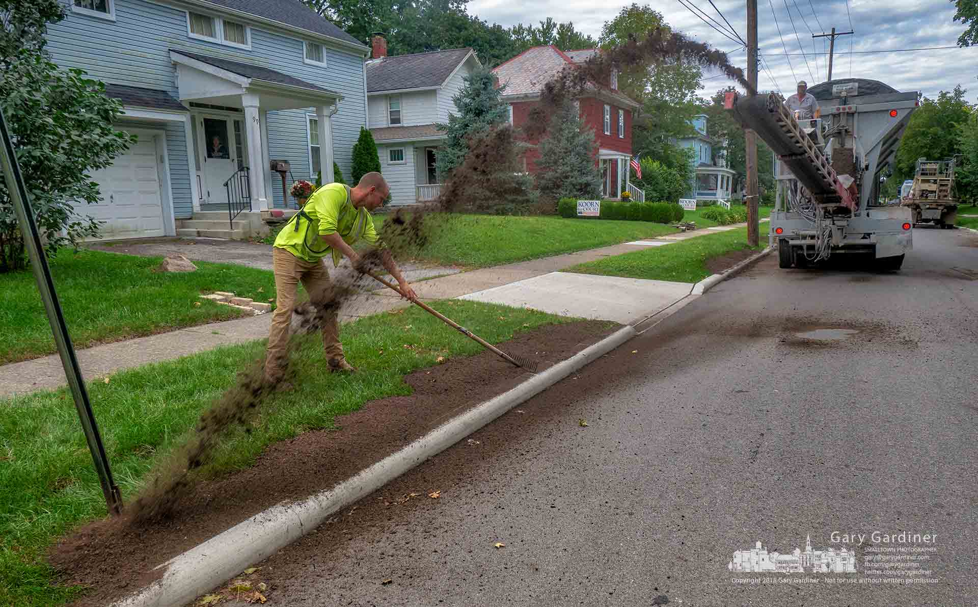 A roadside landscaping crew slings topsoil along the curbs on East Broadway to complete the process of rebuilding the street from State to Vine after laying new grass seed. My Final Photo for Sept. 27, 2018.