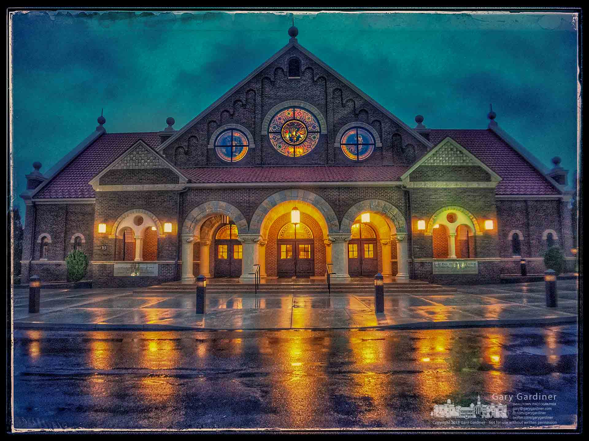 The early morning lights of St. Paul the Apostle Church are reflected in the morning rain puddling in the driveway and sidewalks as parishioners arrive before sunrise for the first Mass of the day. My Final Photo for Sept. 9, 2018.