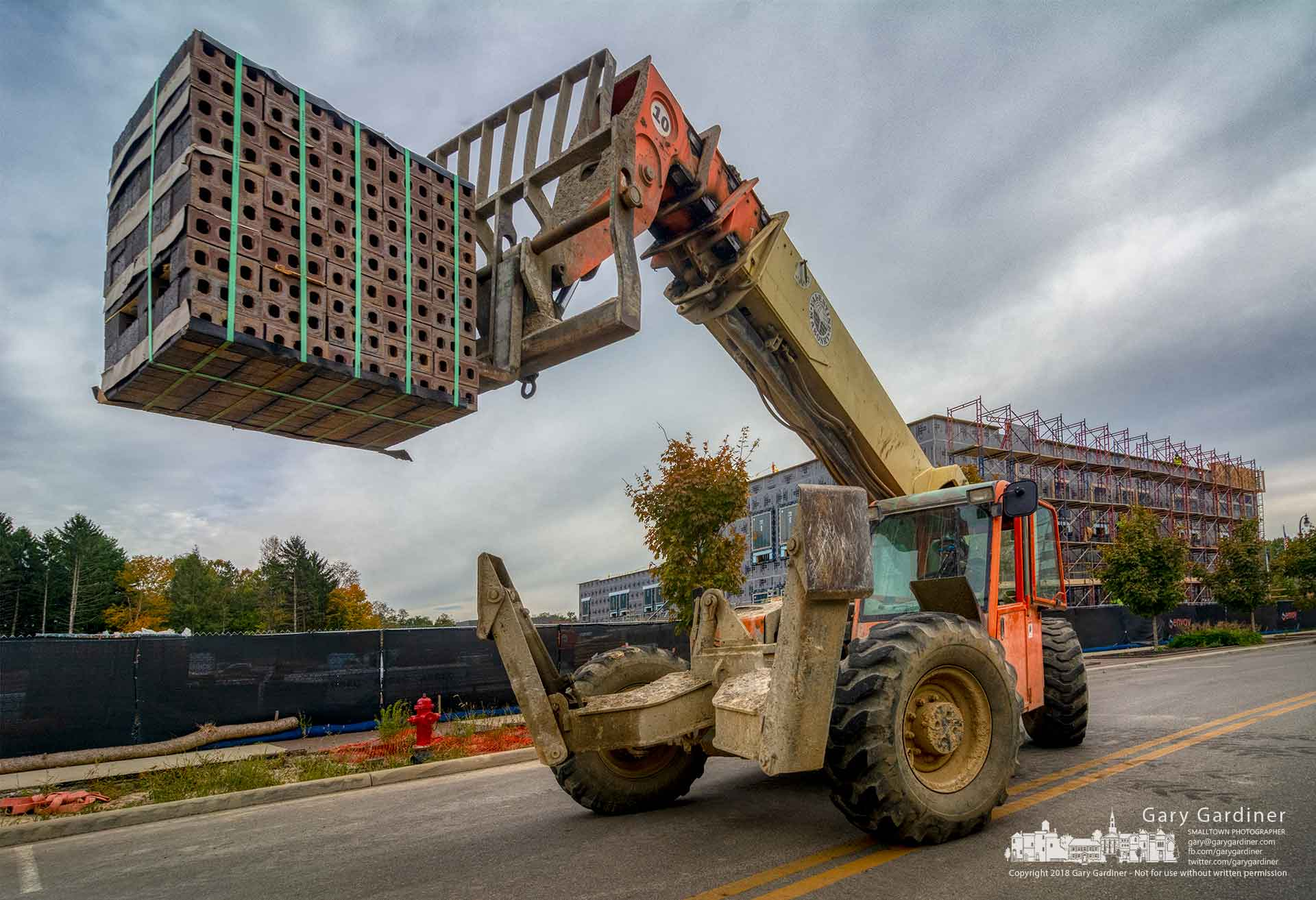 An operator offloads palettes of bricks delivered Thursday to the construction site for the Envoy coworking office building at Meridian Way in Westar. My Final Photo for Oct. 25, 2018.