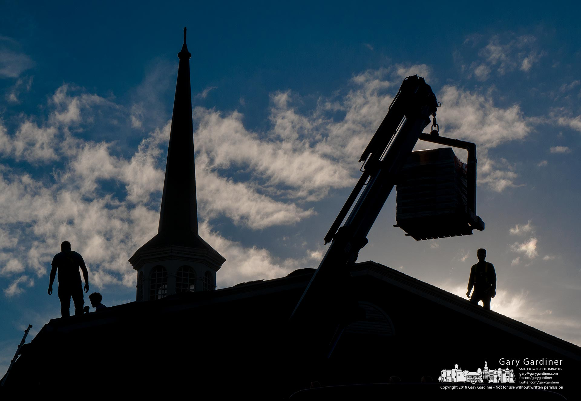 Roofers load a palette of shingles atop the old Church of the Savior building on South State Street where they are replacing shingles on what is now a daycare center. My Final Photo for Oct. 10, 2018.