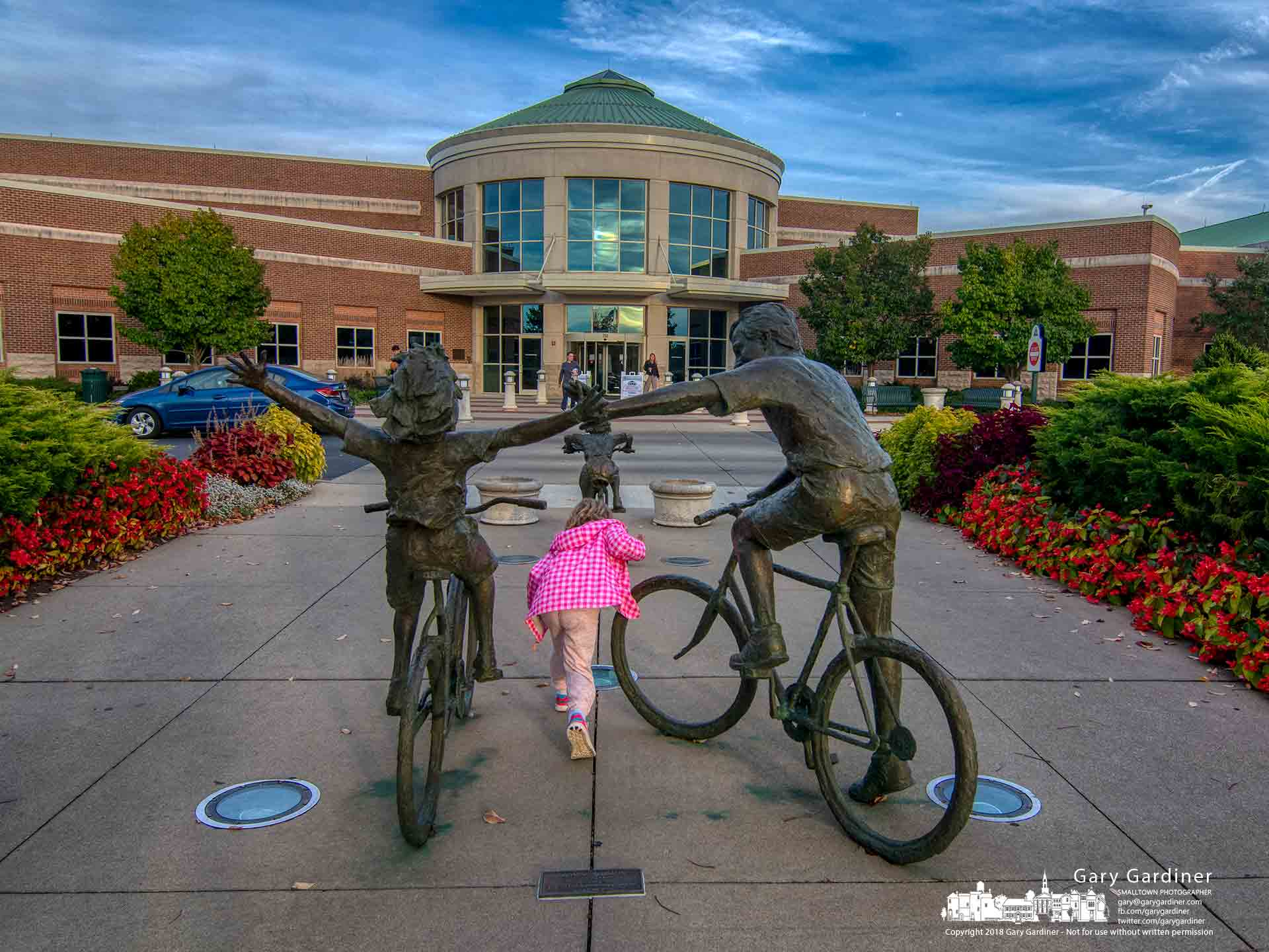 A young girl runs beneath the outstreched arms of a bicycling sculpture at th eentrance to the Westerville Community Center. My Final Photo for Oct. 16, 2018.