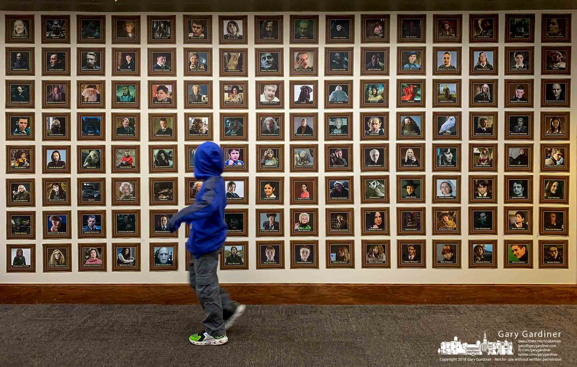 A library visitor runs past a display of Harry Potter movie characters that are displayed as part of the library's Wizards & Wands Festival. My Final Photo for Oct. 20, 2018.