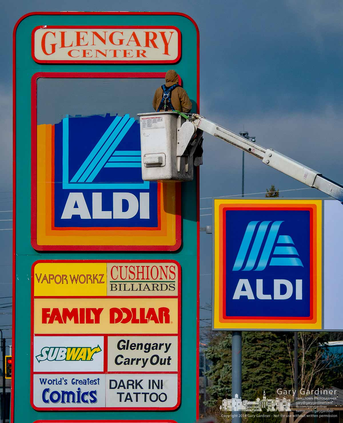 A worker paints over the original Aldi grocery store sign at Glengary Center after completing the addition of signage for the new Aldi set for a grand opening Thursday morning. My Final Photo for Nov. 28, 2018.