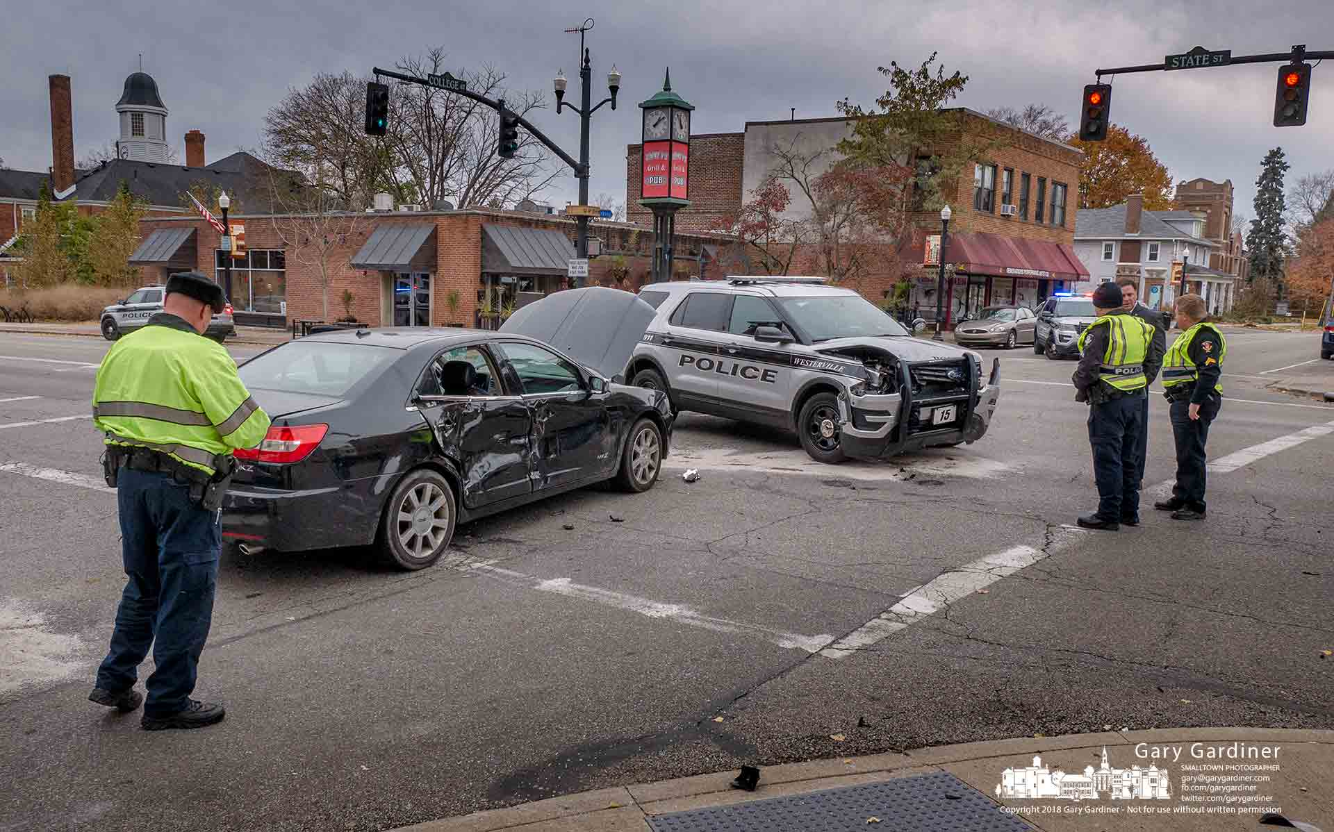 A police officer, at left, photographs the scene of a police cruiser crash at State and College during an emergency run. My Final Photo for Nov. 14, 2018.
