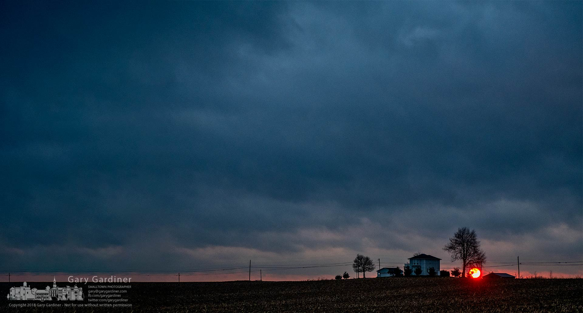The sun breaks through a sliver of clear sky at the edge of rainy cloud cover just as it settles into the sunset behind an old farmhouse near Johnstown, Ohio. My Final Photo for Nov. 24, 2018.
