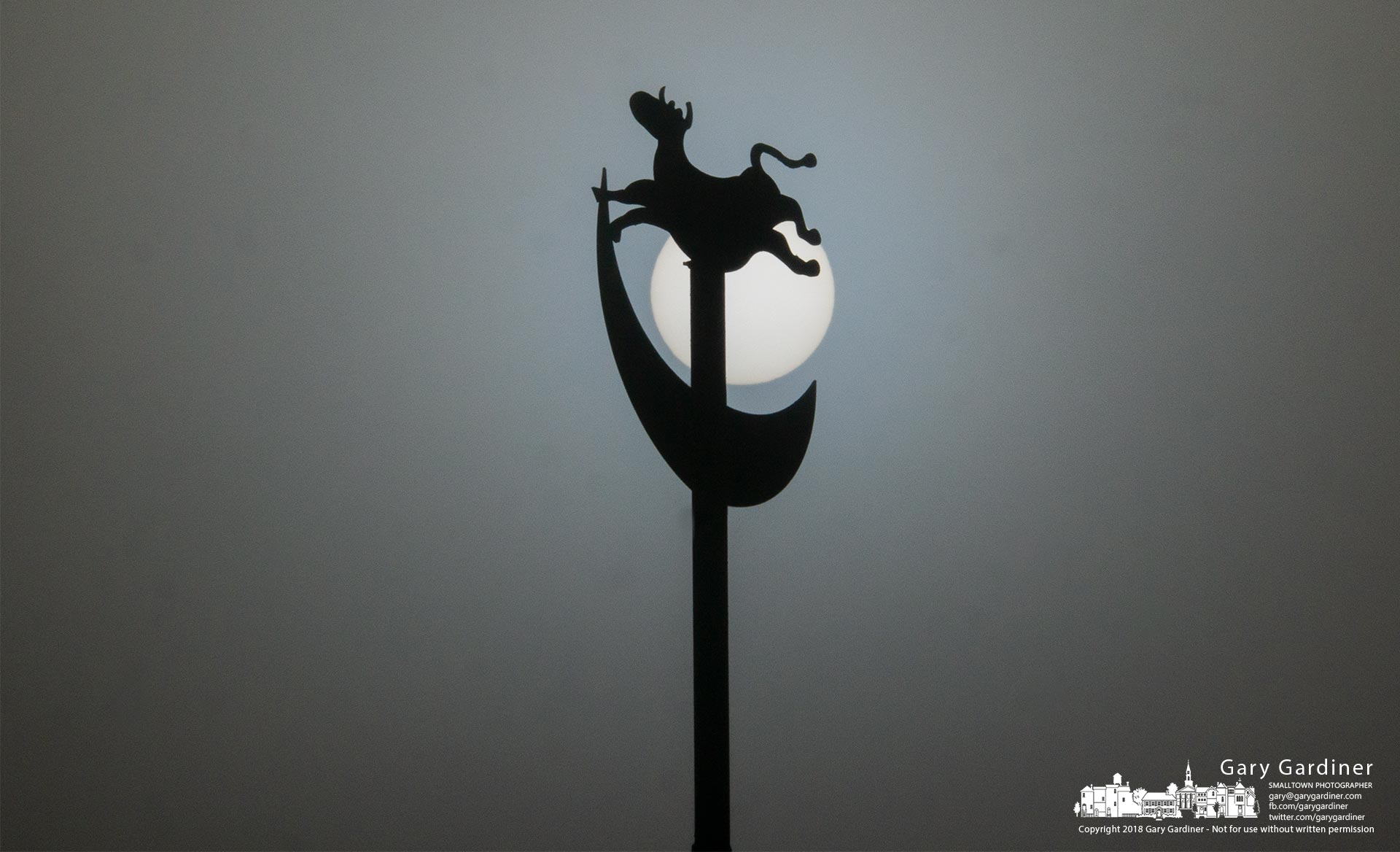 The fog-shrouded sun silhouettes Children'sHospital's cow jumpingover the moon weathervane on a crisp morning after Christmas. My FinalPhoto for Dec. 26, 2018.