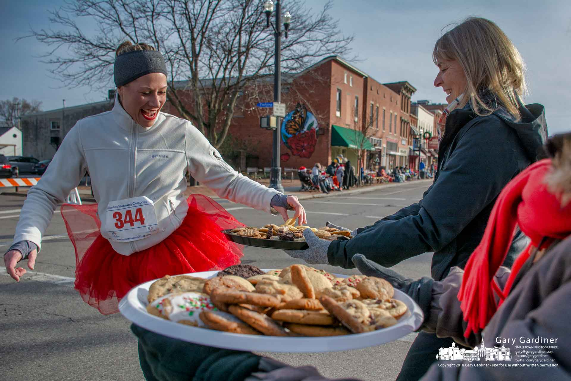A Rudolph Run 5K runner smiles as she grabs her choice of cookie from trays offered to runners near the completion of the race before the Christmas parade. My Final Photo for Dec. 9, 2018.