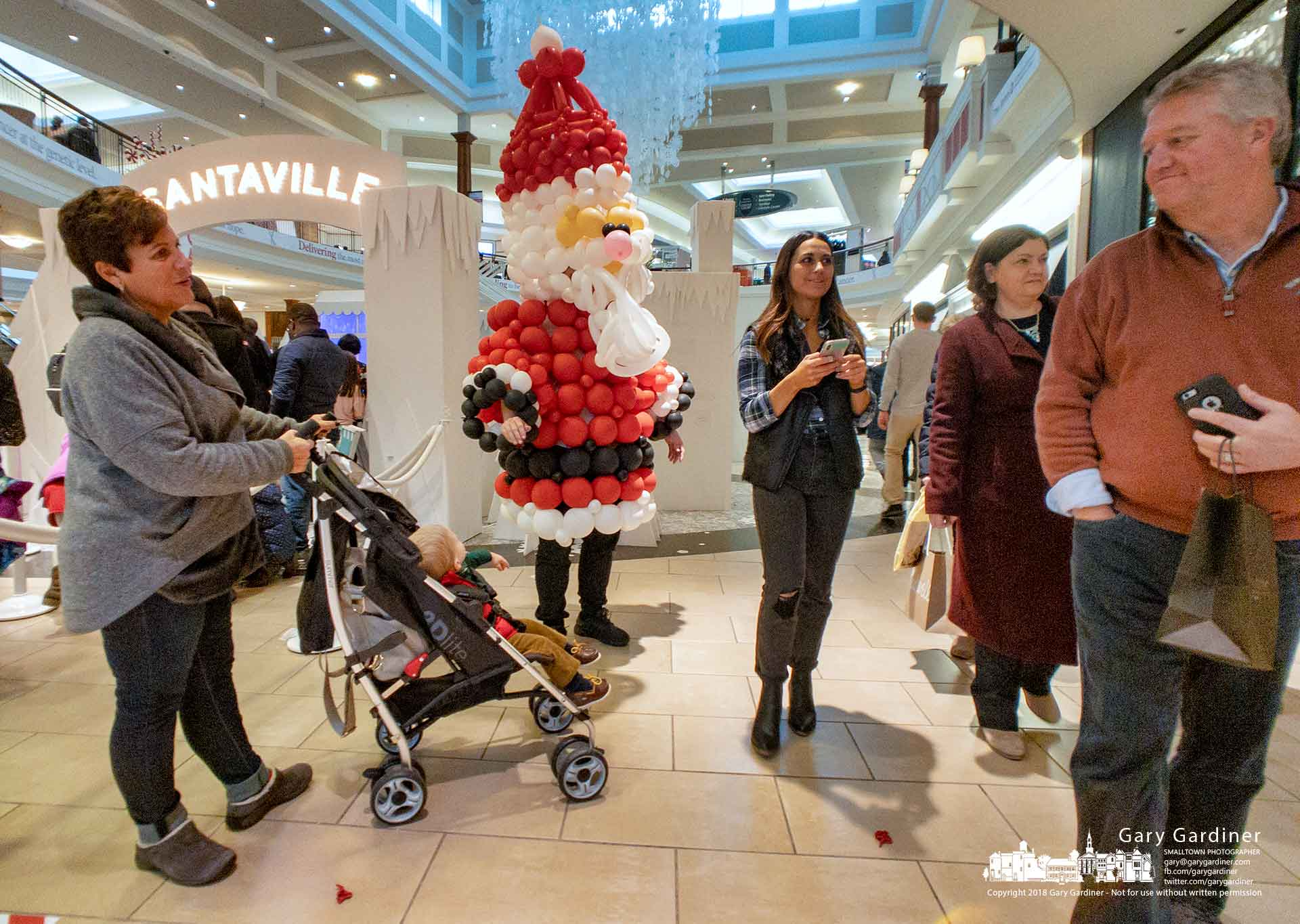 A Santa draped in a balloon sculpture stands ready to receive passers-by at the entrance to the booth for photos with Santa at Polaris Mall. My Final Photo for Dec. 23, 2018.