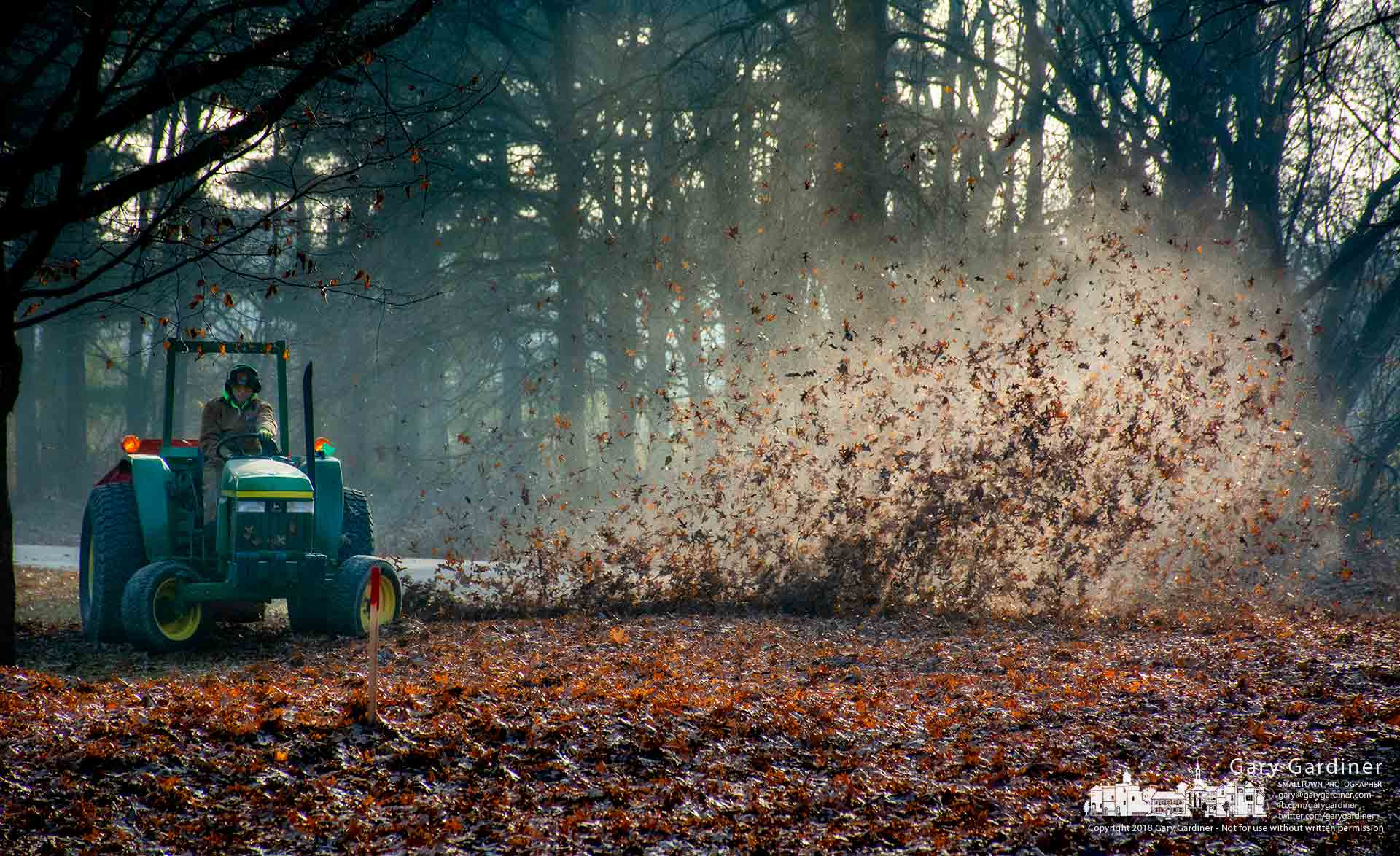 A Metro Parks worker clears leaves from a section of Sharon Woods with a large blower pulled behind a tractor. My Final Photo for Dec. 11, 2018.