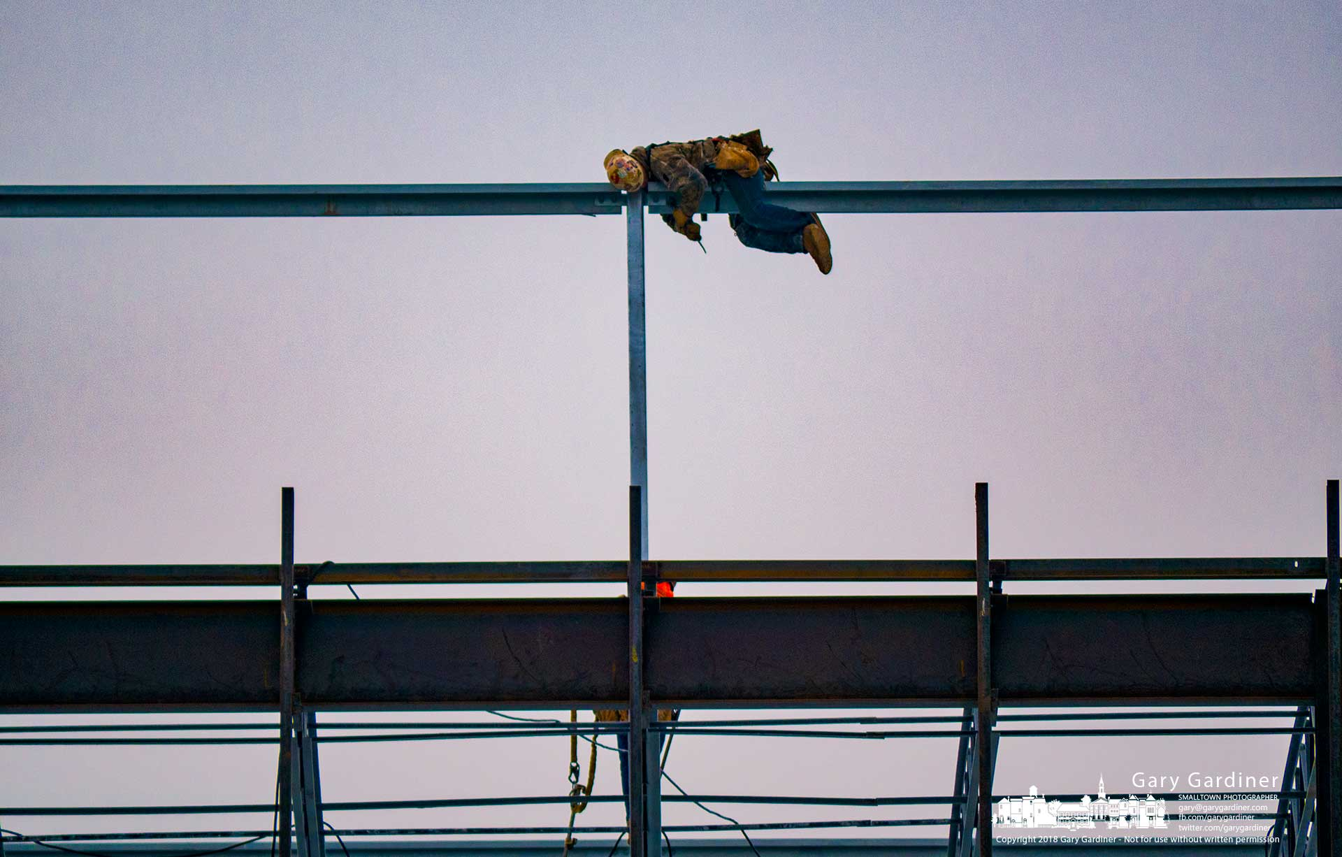 A steelworker bends beneath a steel beam to attach it to post at the DHL building construction site. My Final Photo for Dec. 10, 2018.