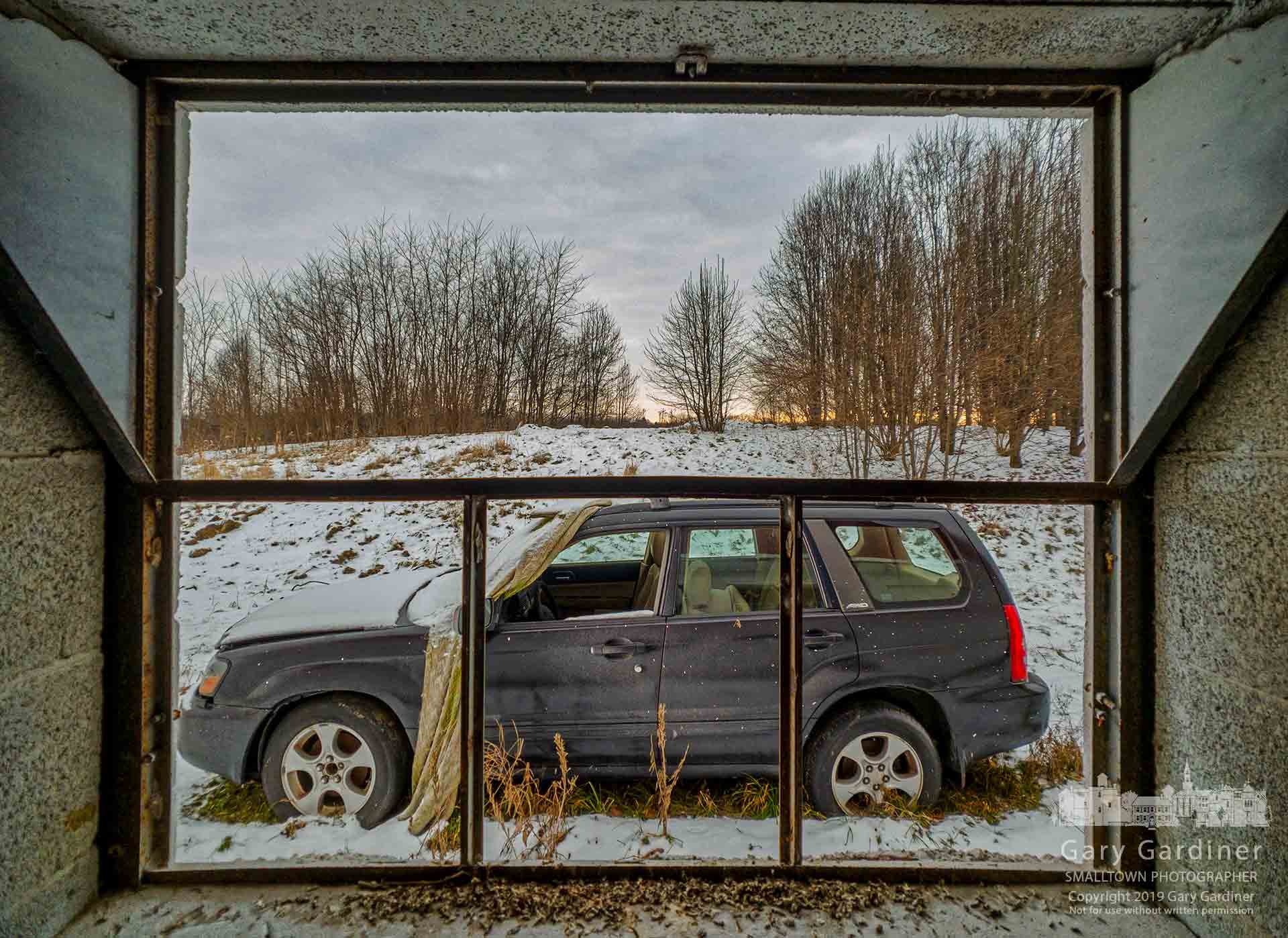 A broken car sits outside the broken windows of the barn on the Braun Farm property in Cleveland Ae at Cooper Road. My Final Photo for Jan. 28, 2019.