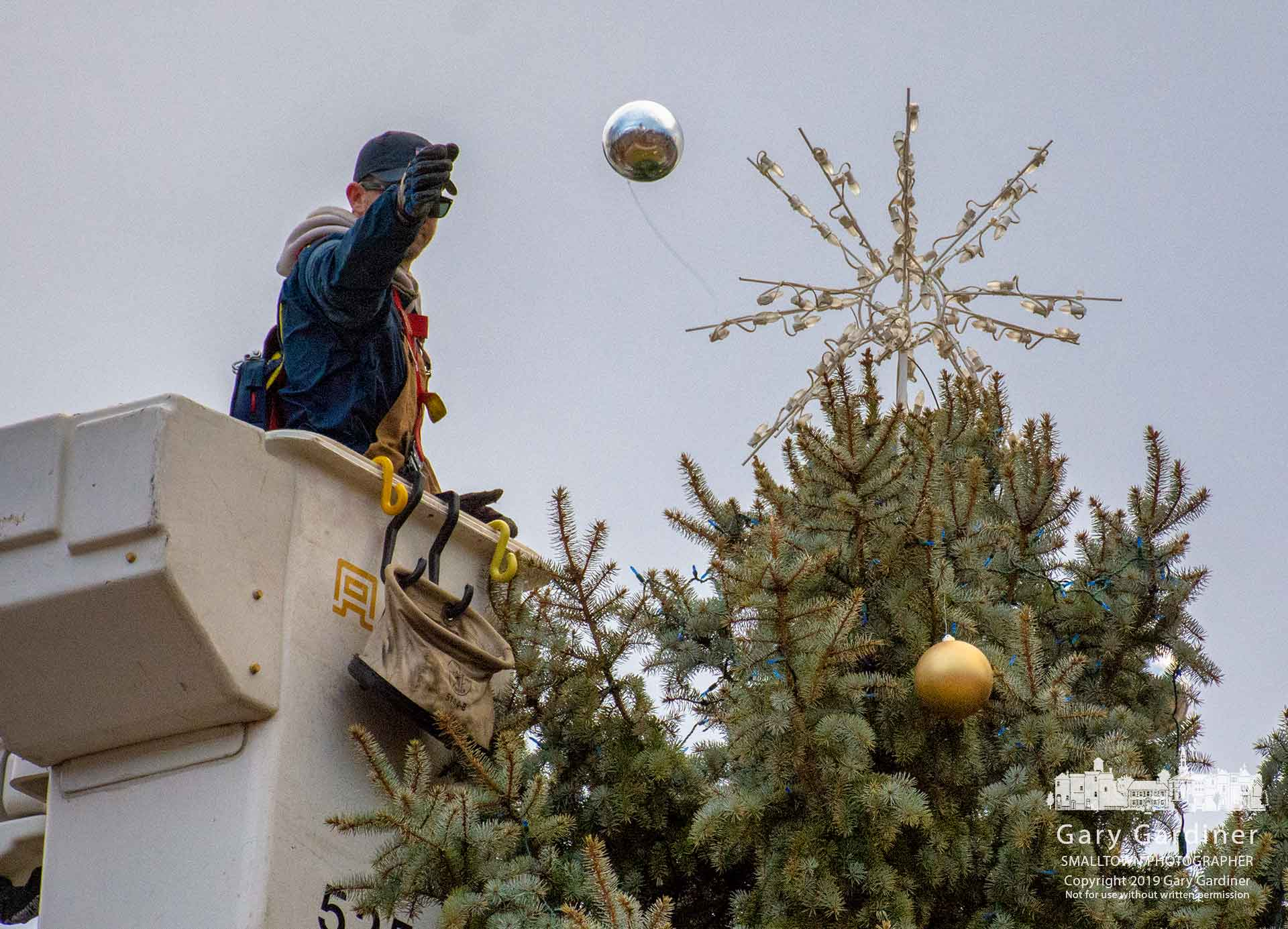 A city electric worker tosses an ornament to another worker on the ground as the holiday tree in front of city hall is removed at the end of the Christmas season. My Final Photo for Jan. 7, 2019.