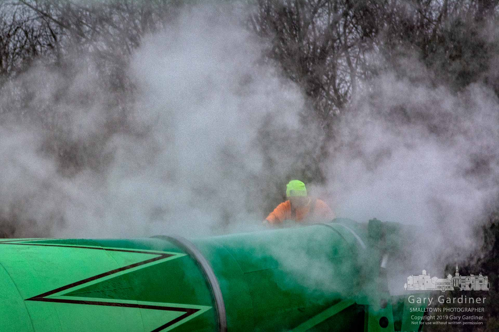 A concrete truck operator works in a cloud of water condensation rising from his truck as he cleans it after delivering a morning load to the DHL construction site. My Final Photo for Jan. 11, 2019.