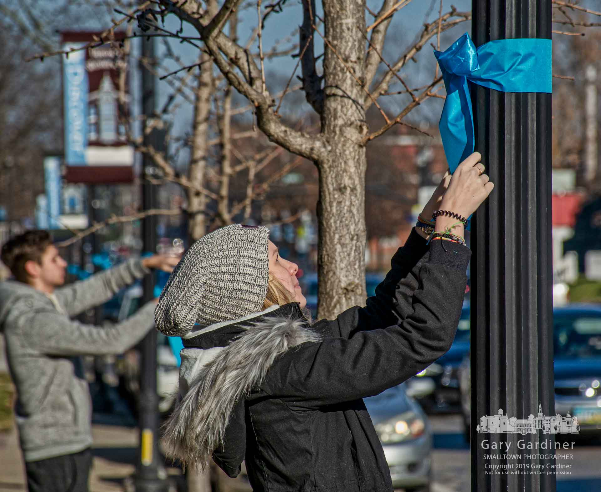 Volunteers tie teal bows to utility poles and trees in Uptown Westerville marking Cervical Cancer Awareness Month with a program named Paint the Town Teal. My Final Photo for Jan. 5, 2019.