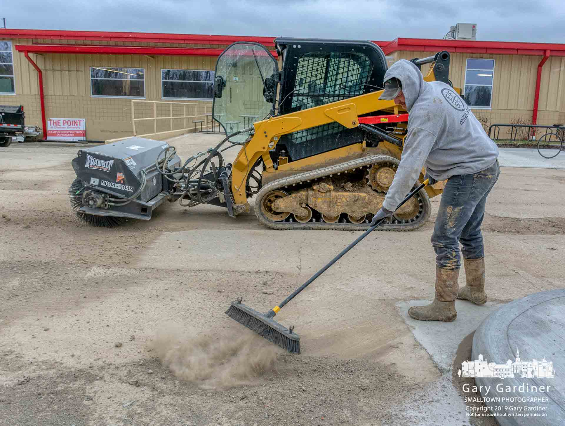 A construction worker stepped away from his powered sweeper and took to a push broom to clear debris from the edges of the loading dock section of the recently upgraded section of the parking lot and walkways at The Point on the Otterbein University. My Final Photo for Jan. 9, 2019.