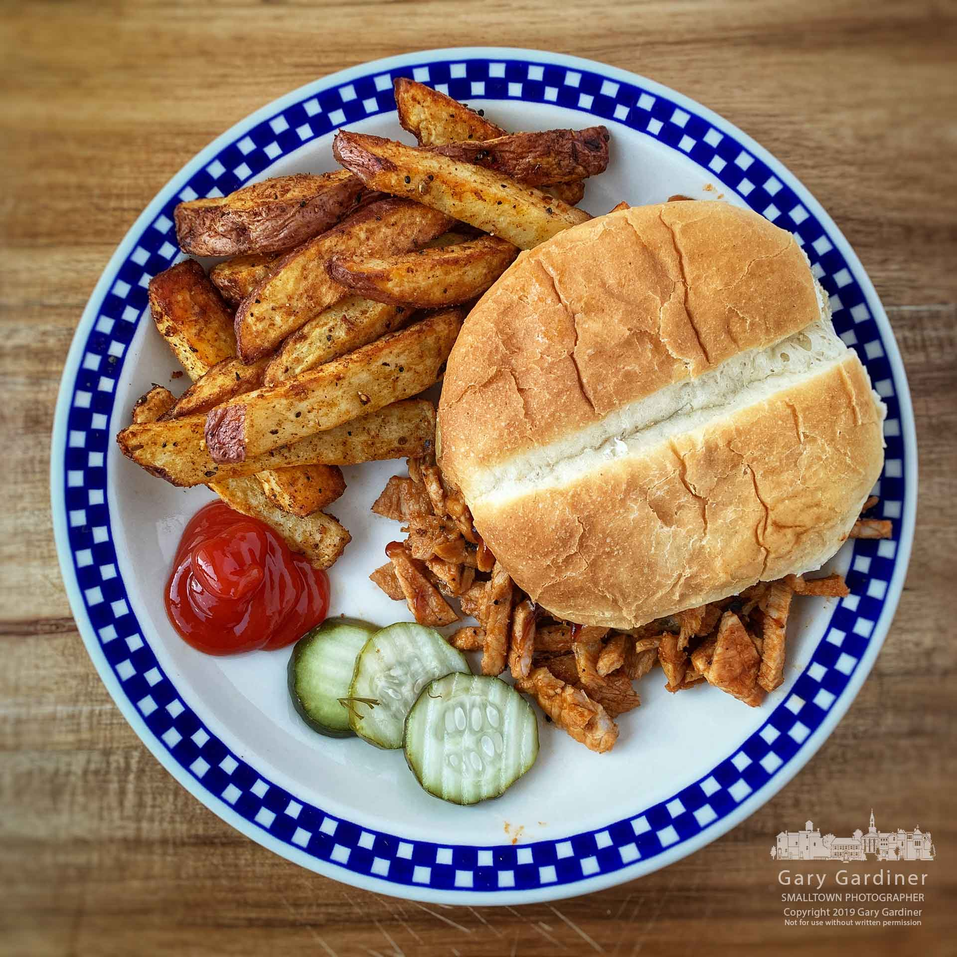 A dinner of BBQ leftover sliced and shredded pork roast, air-fried potatoes, garlic dill pickles, and sourdough bun. My Final Photo for Feb. 24, 2019.