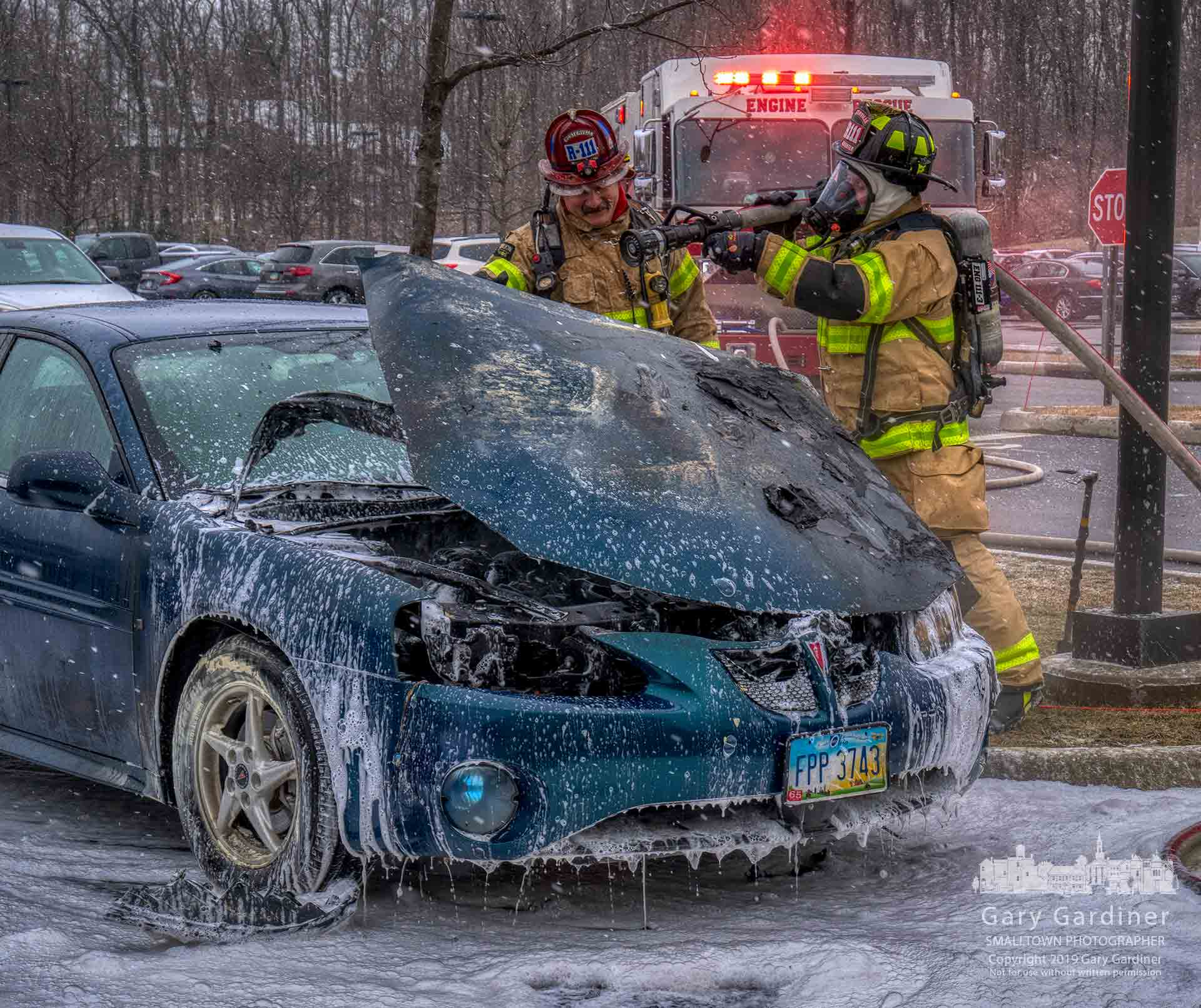 Westerville firefighters spray water on hot spots on the engine of a car that burned in the parking lot of Ohio Health on Polaris Parkway. My Final Photo for Feb. 18, 2019.