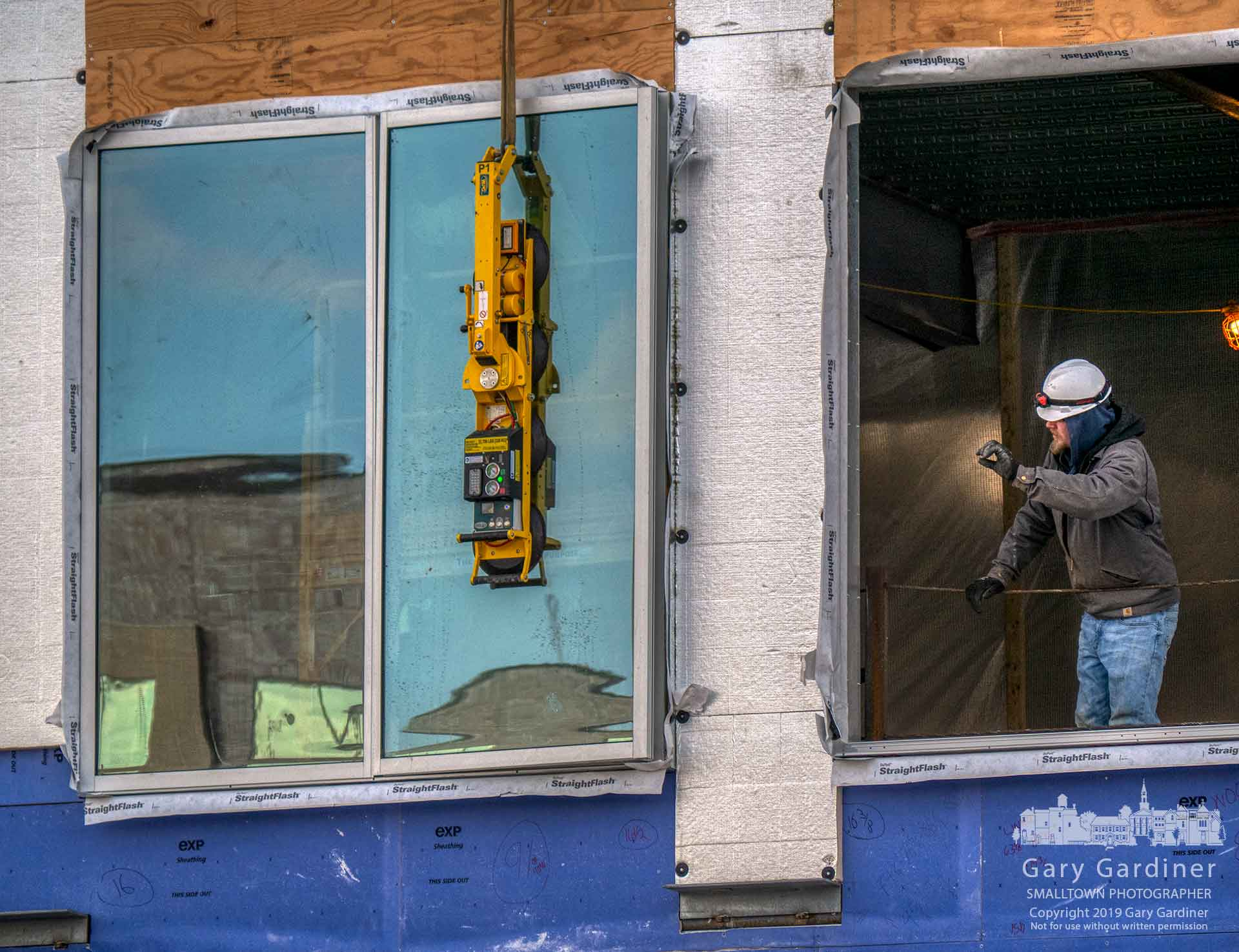 A construction worker signals instructions to a crane operator movinga window into position for installation at the DHL building being built in Westar. My Final Photo for Feb. 21, 2019.