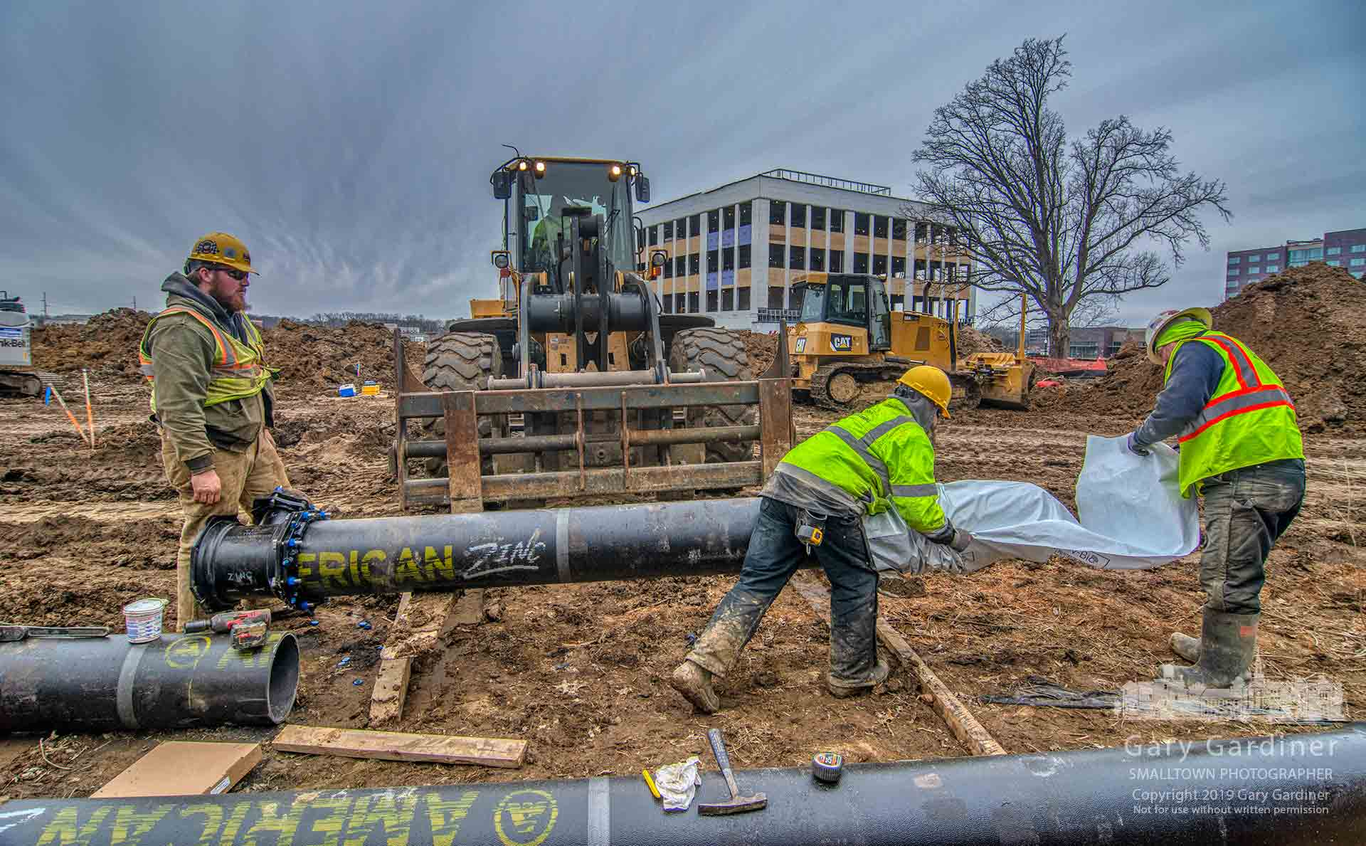 A work crew sleeves a 12-inch water pipe before installing it as part of new underground utility service for the DHL building being built in Westar. My Final Photo for Feb. 28, 2019.